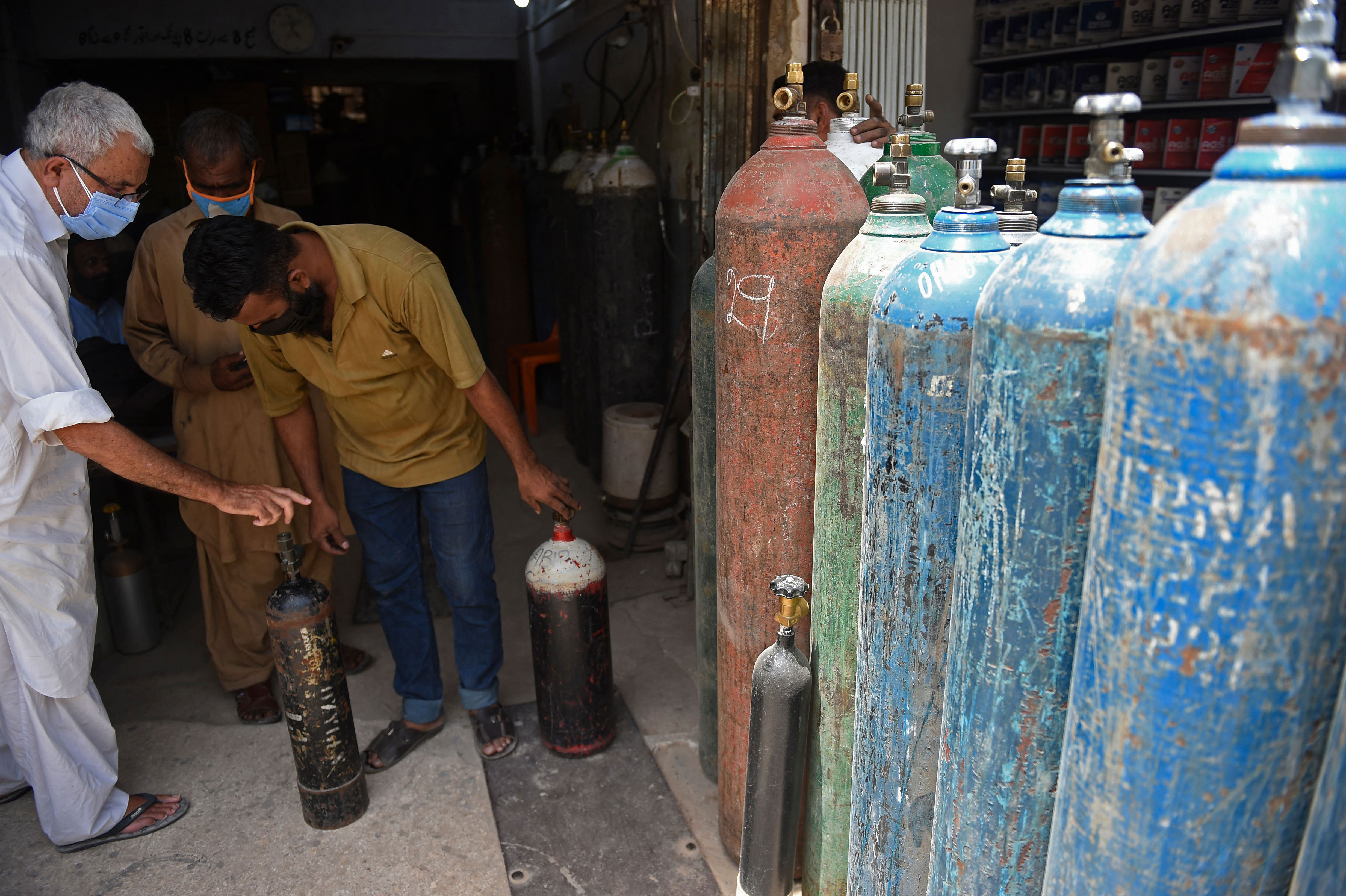 A shopkeeper speaks with a customer before refilling oxygen cylinders for Covid-19 patients in Karachi, Pakistan, on April 26.