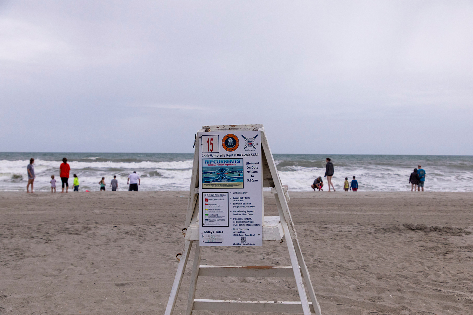 Beachcombers look towards the sea at dawn in North Myrtle Beach where a lifeguard stand warns of rip currents. Tropical Storm Isais is moving up the east coast and is expected to make landfall near Myrtle Beach, S.C., on Monday, Aug. 3