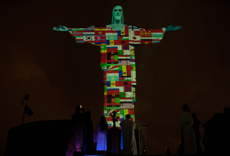 Rio's Christ the Redeemer statue is lit up with the flags of countries currently afflicted by the coronavirus in Rio de Janeiro, Brazil, Wednesday, March 18.