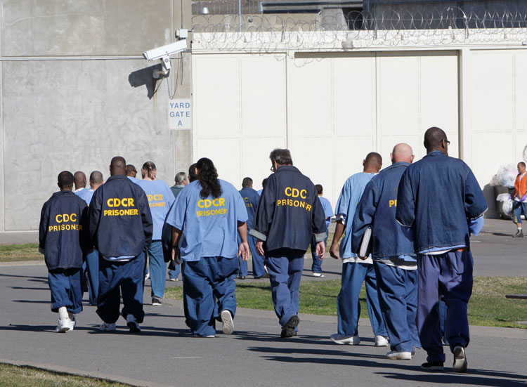 In this February 26, 2013 file photo, inmates walk through the exercise yard at California State Prison Sacramento, near Folsom, California.
