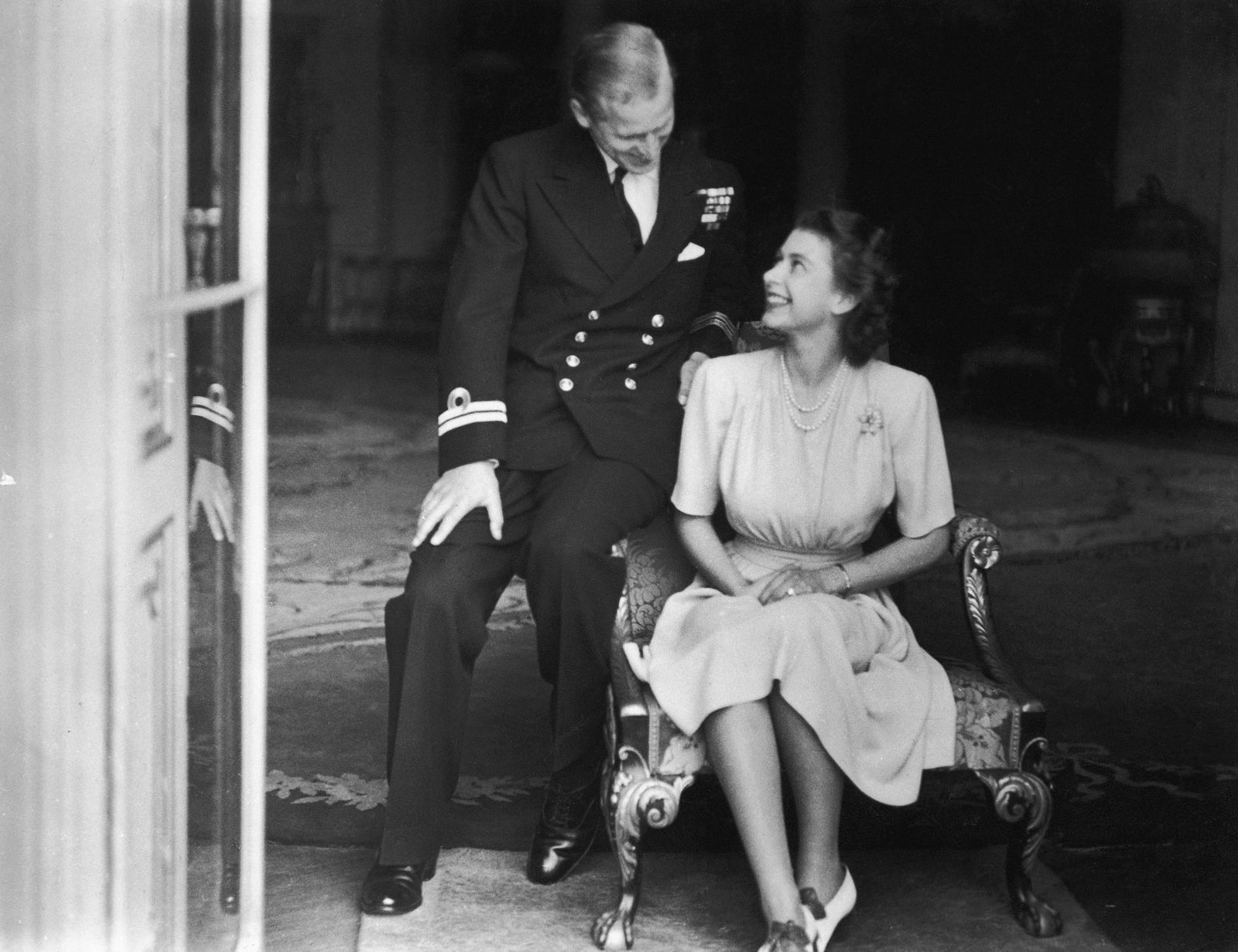 Prince Philip sits with his fiancee, Princess Elizabeth, in July 1947. He had become a naturalized British citizen and a commoner, using the surname Mountbatten, an English translation of his mother's maiden name. He was also an officer in the British Royal Navy and fought in World War II.