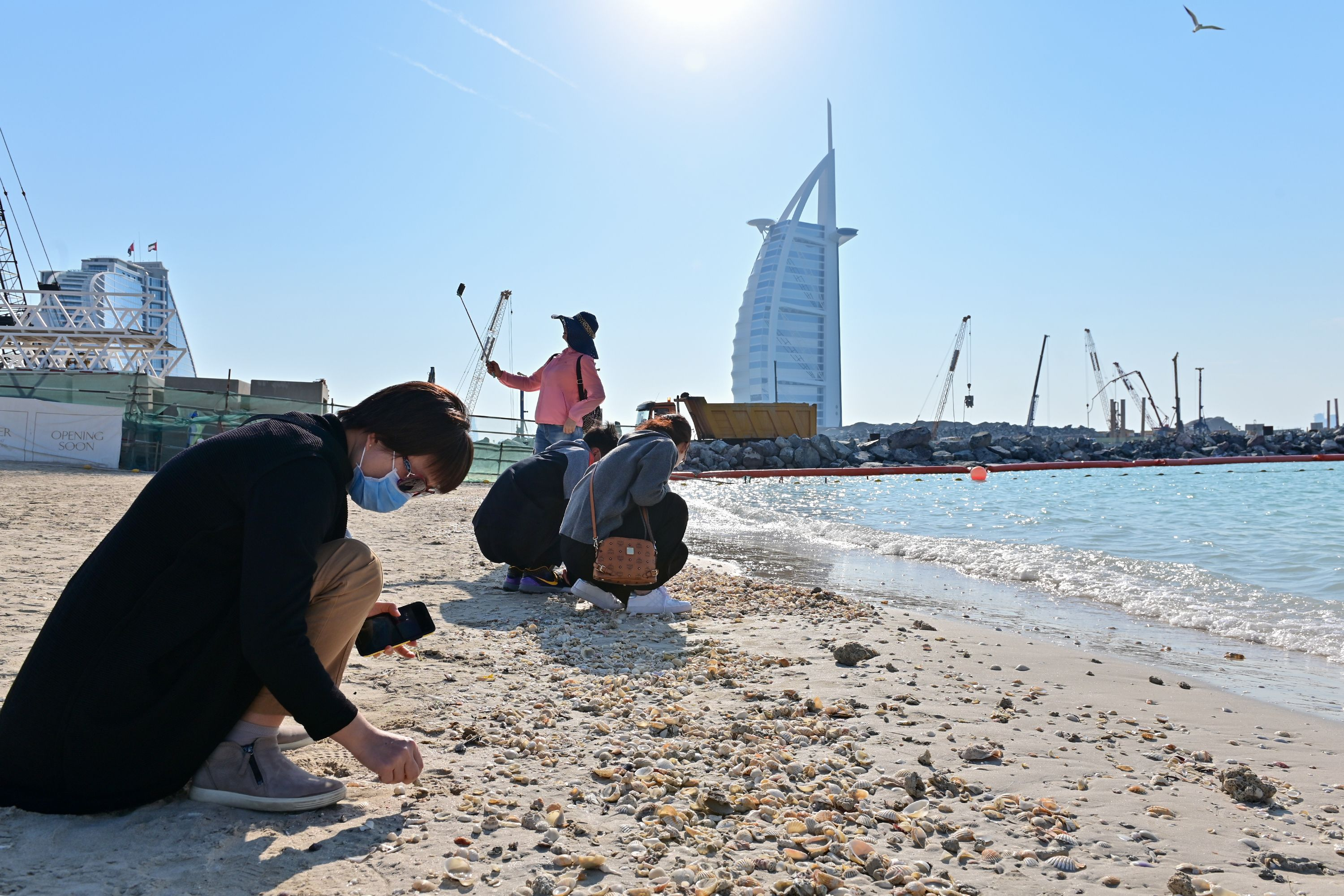 Tourists wearing surgical masks search for seashells on a beach next to Burj Al Arab in Dubai.