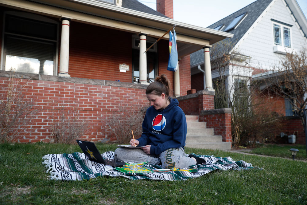 Lisa Condor sits on a blanket in her front yard as she works online on her masters in business administration from Colorado State University as a statewide stay-at-home order remains in effect in an effort to reduce the spread of the new coronavirus on Monday, March 30, in Denver.