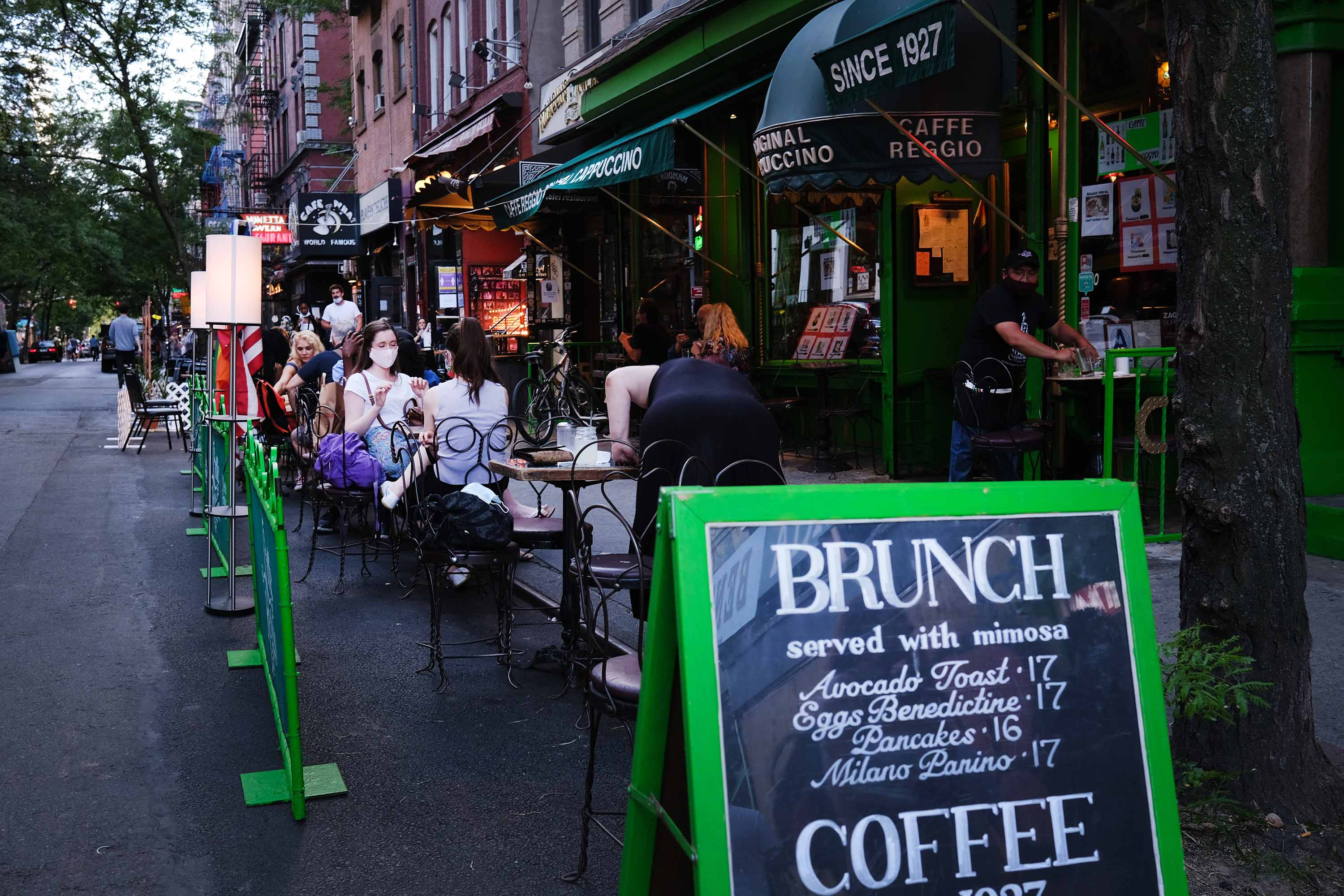 People dine at tables placed outside of a Manhattan restaurant in New York, on June 24.