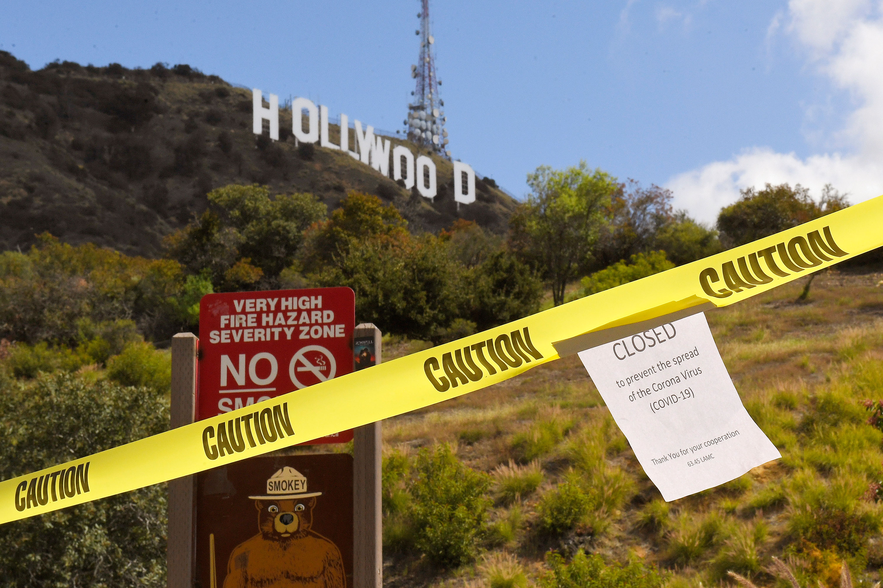 A sign about the closure of the Innsdale Trail is posted at the trail's entrance near the Hollywood sign in Los Angeles on March 28.