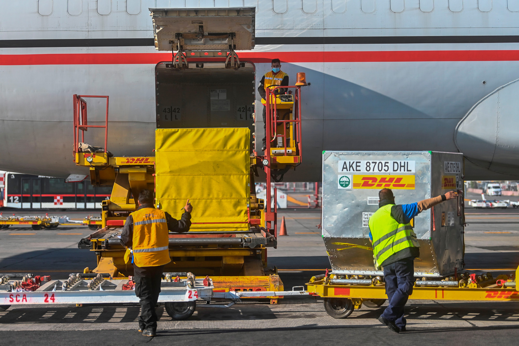 Workers unload containers carrying a shipment of the Pfizer/BioNTech COVID-19 vaccine at Benito Juarez International Airport in Mexico City on December 26, 2020.