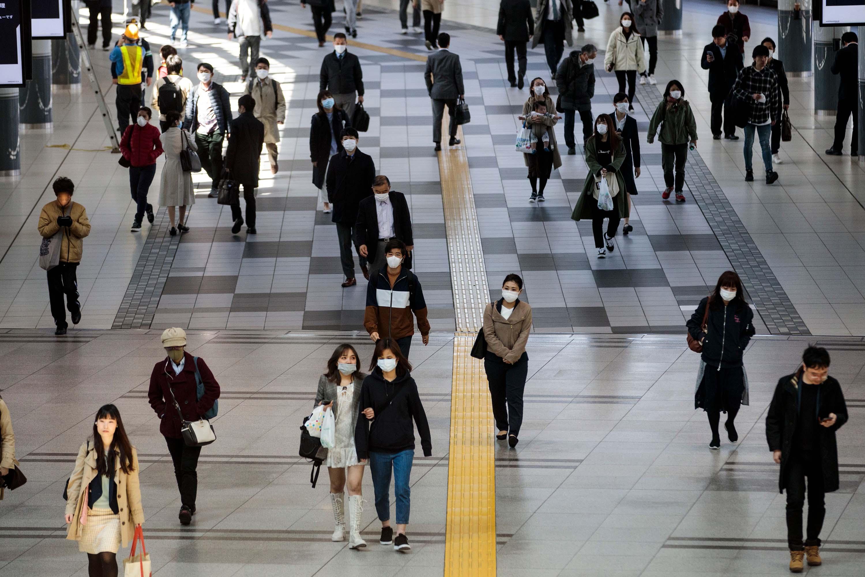 Commuters wearing face masks pass through Shinagawa station in Tokyo, Japan, on April 6.