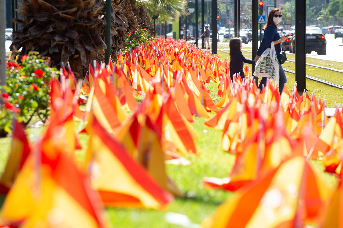 A woman walks with her daughter next to an installation at Isidoro Medina Park by the National Association of Victims and People Affected by Coronavirus (ANVAC) on October 18, in Murcia, Spain. The Spanish flags are a tribute to COVID-19 deaths in the country.
