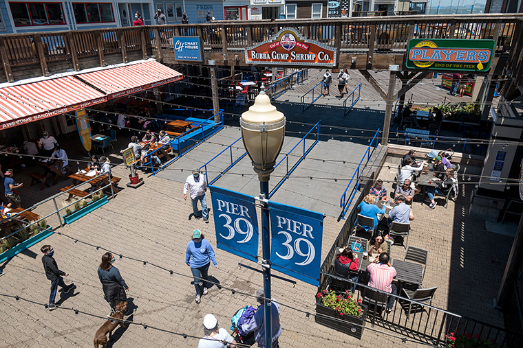 People sit at restaurants on Pier 39 in San Francisco, California, on Monday, June 22.