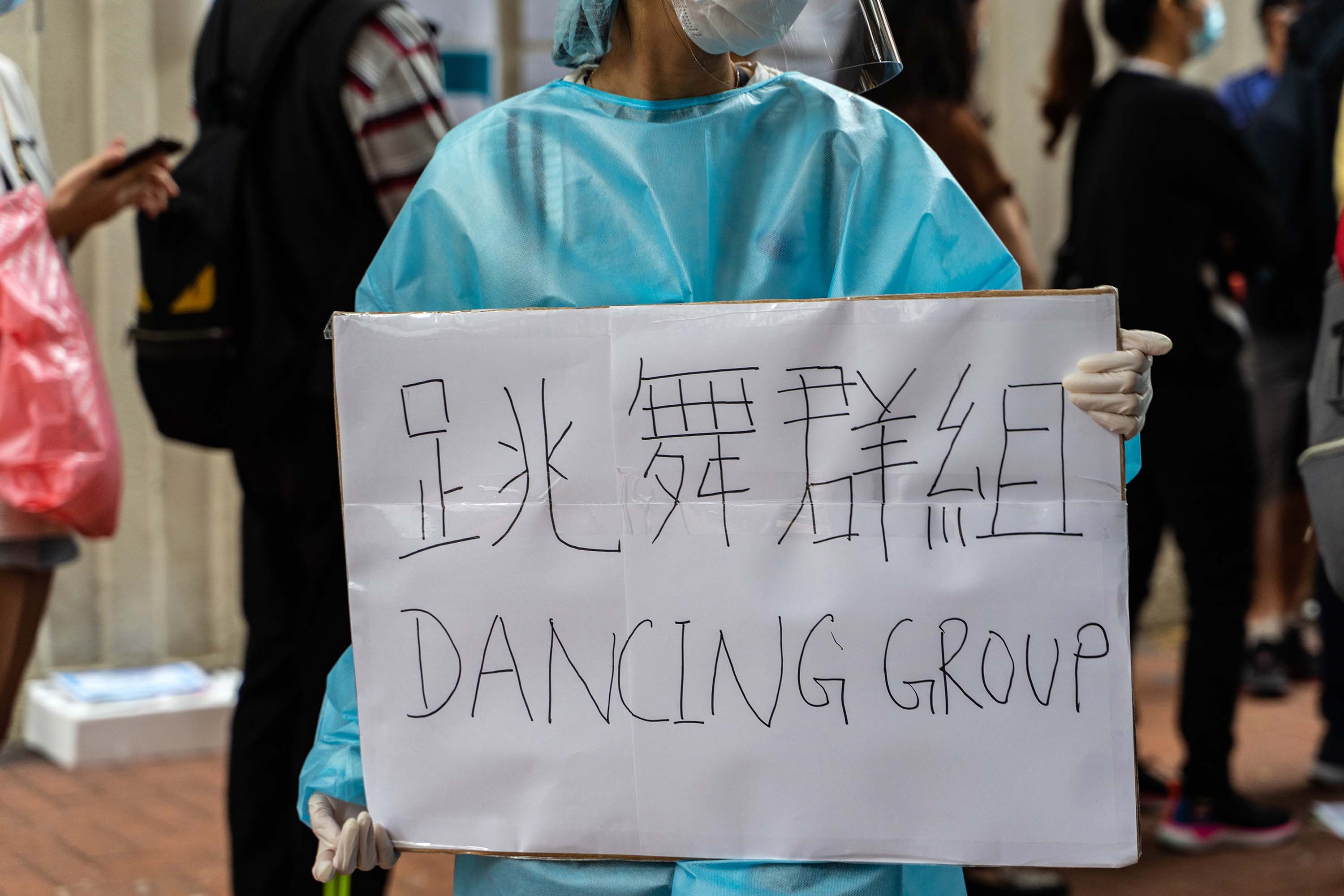 "A health care worker holds a sign reading ""Dancing Group,"" referring to the dance club coronavirus cluster, as people line up at a testing center in the Yau Ma Tei district of Hong Kong on Monday."
