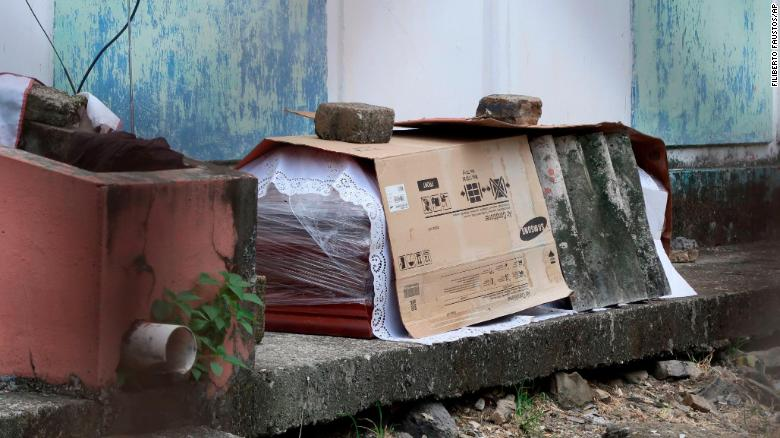 A coffin containing the body of a person who is supposed to have died from Covid-19 lays wrapped in plastic and covered with cardboard, outside a block of family apartments in Guayaquil on April 2.