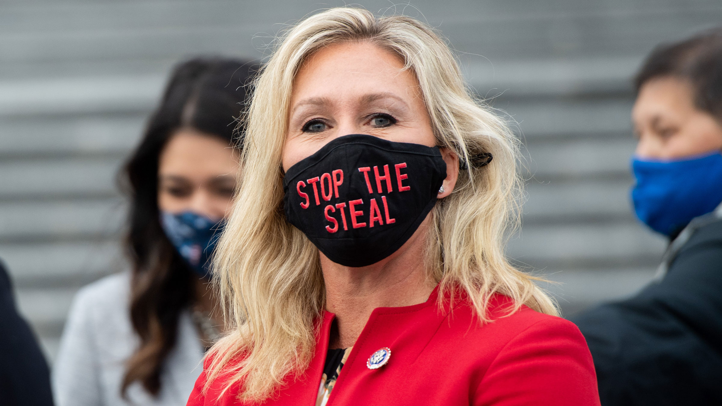 """US Rep. Marjorie Taylor Greene wears a """"Stop the Steal"""" mask while speaking with fellow first-term Republican Congress members on the steps of the US Capitol on Monday."""