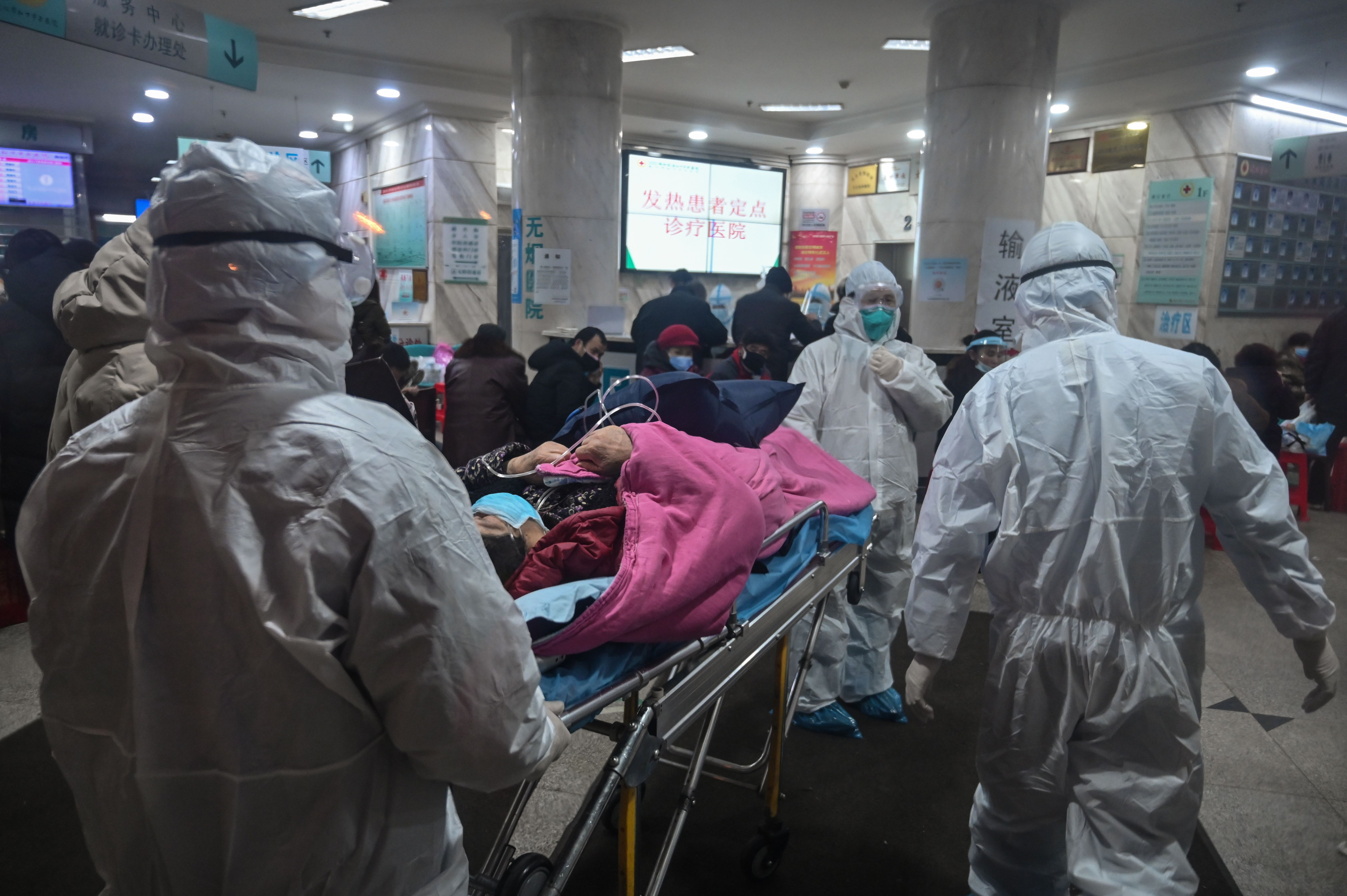 Medical staff wearing protective clothing arrive with a patient at the Wuhan Red Cross Hospital in Wuhan on January 25.