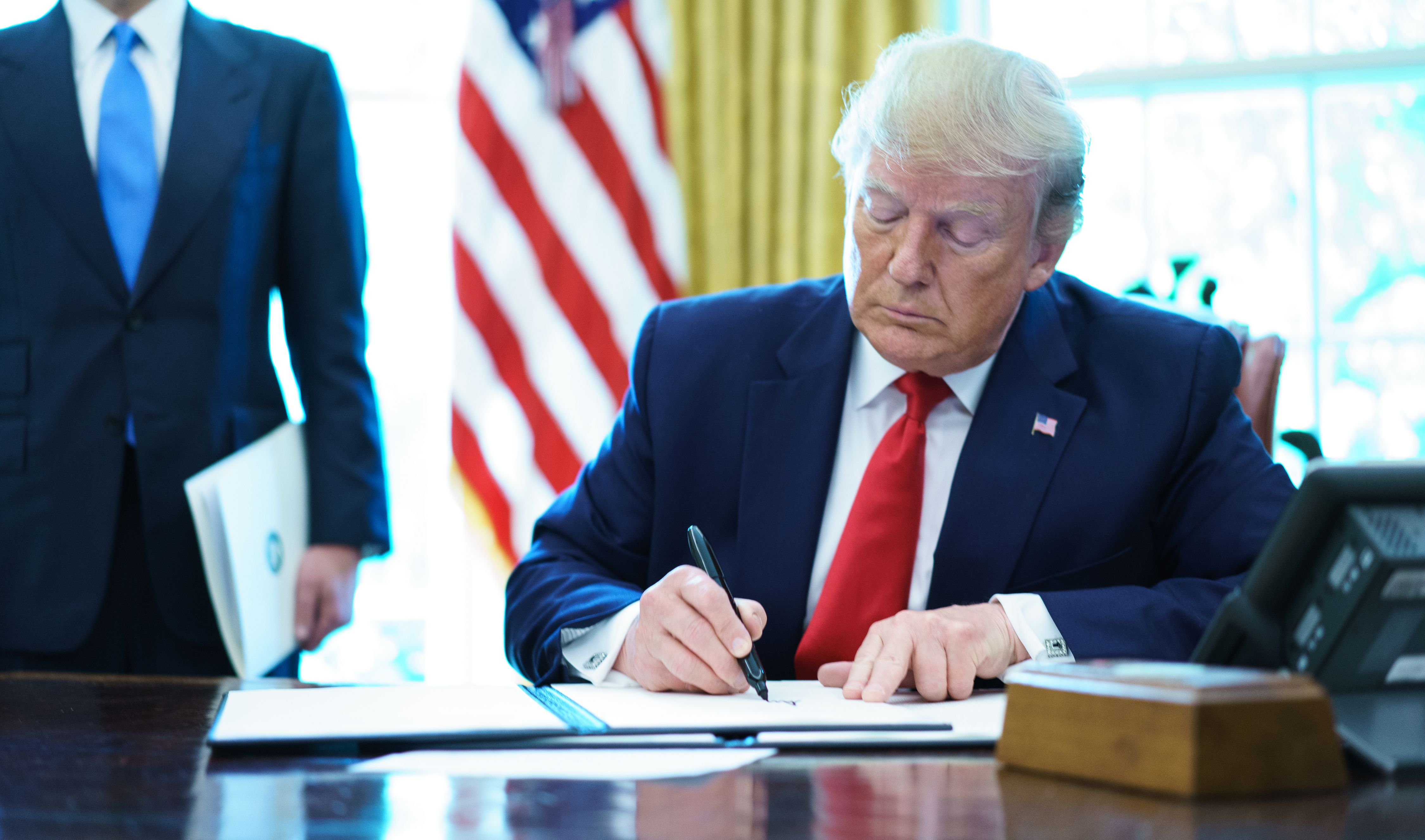 President Trump signs an executive order on Iran sanctions in the Oval Office of the White House on June 24, 2019.