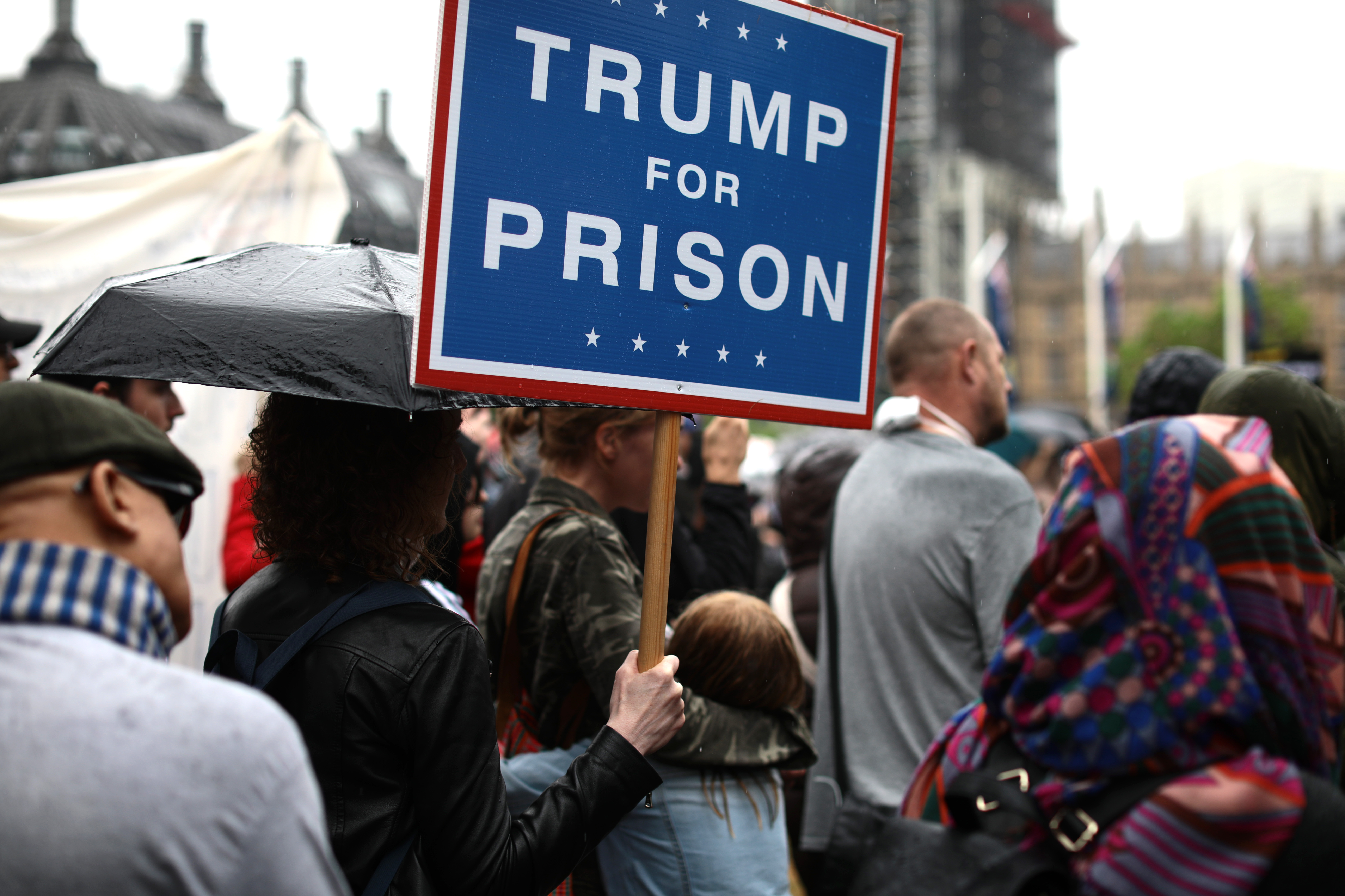 Protesters holding placards stand in the rain at Parliament Square as President Trump and first lady Melania Trump visit 10 Downing street for a meeting on June 4, 2019 in London.