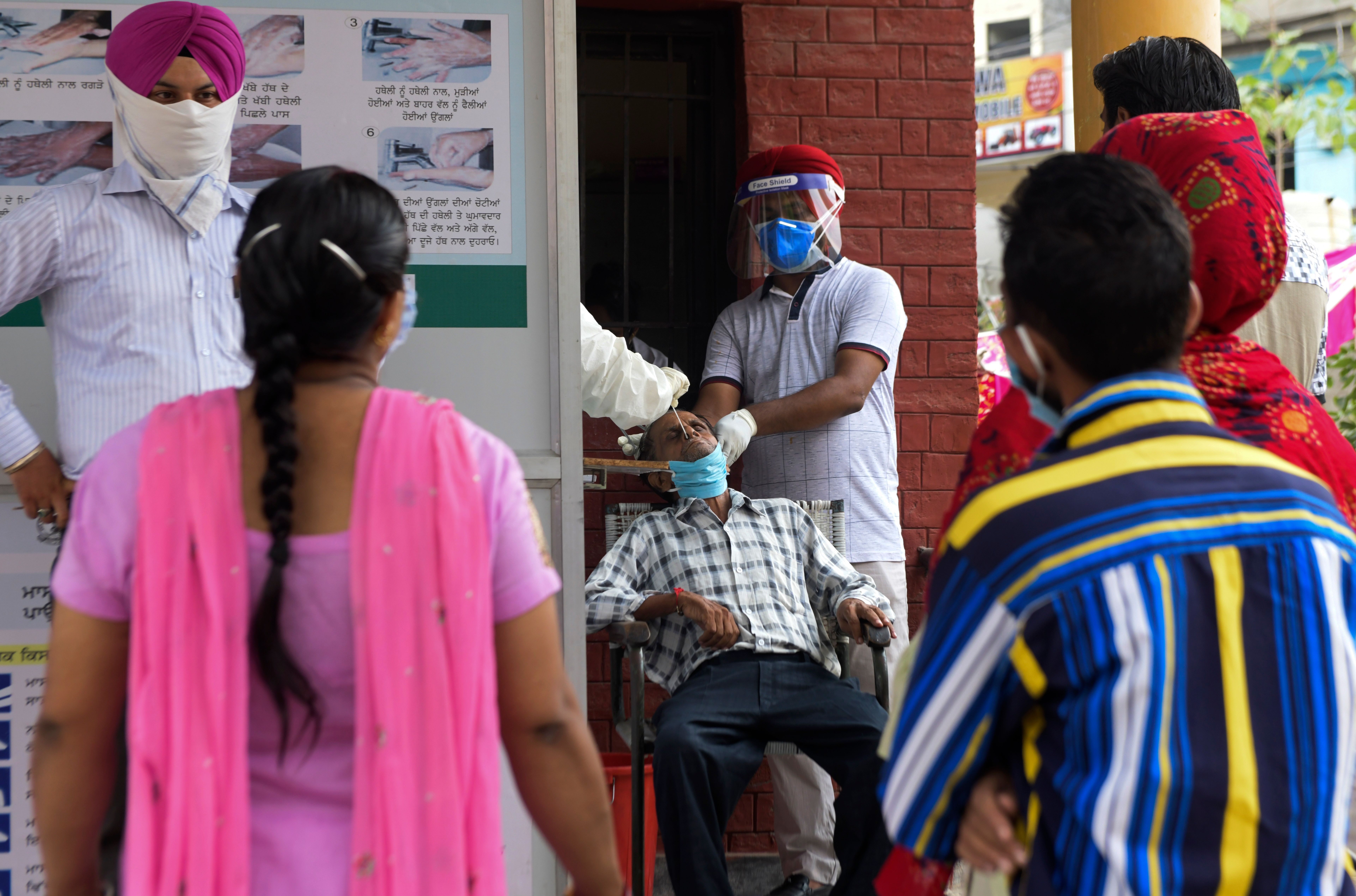 Health officials at a hospital in Amritsar, India, collect a nasal swab sample to test for Covid-19 on September 2.
