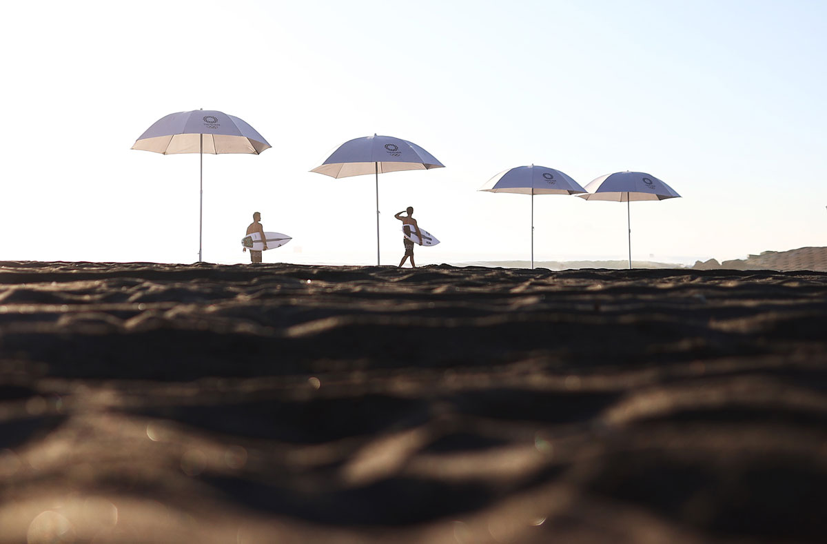 Surfers arrive for a practice session at Tsurigasaki Surfing Beach on July 23.