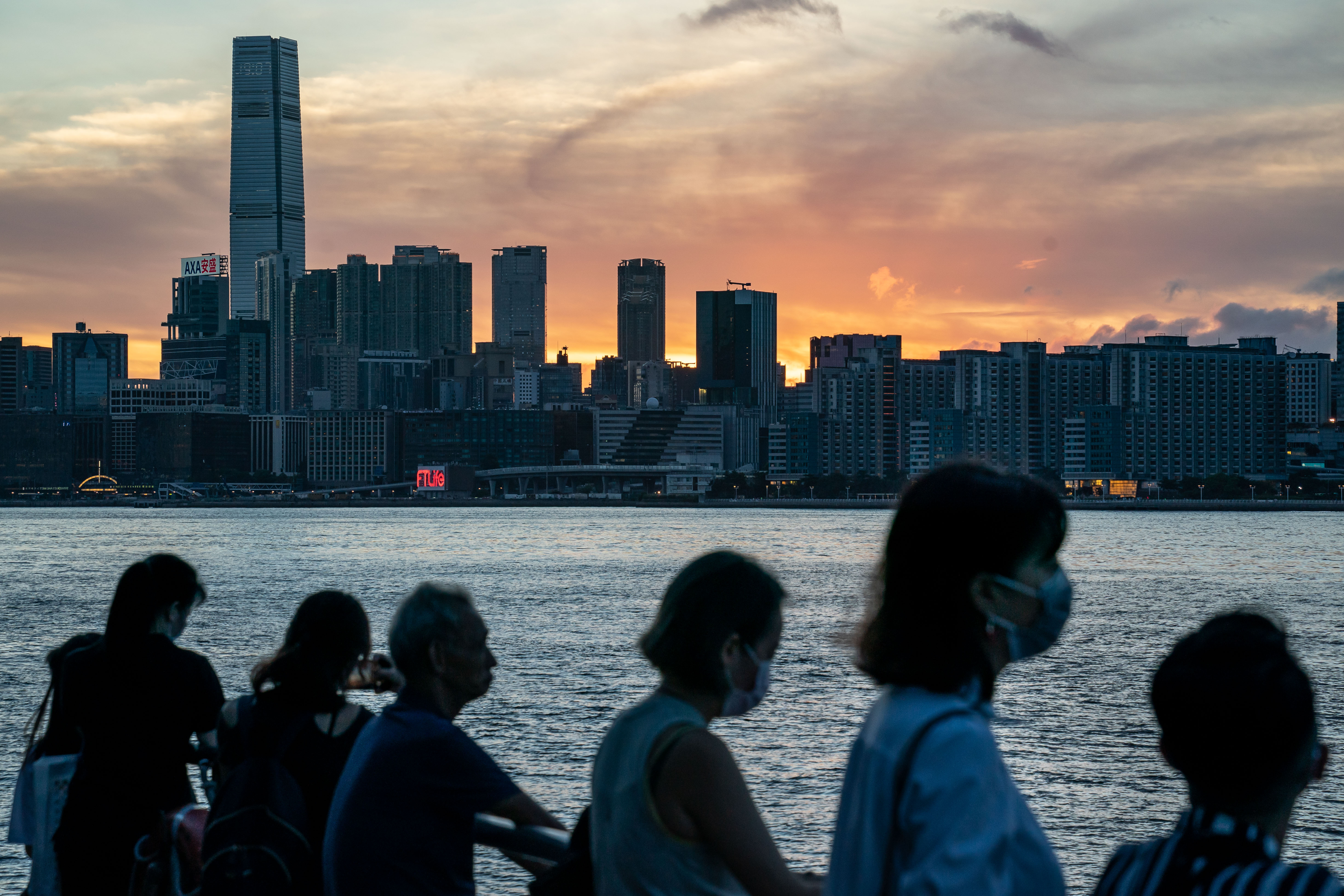 People stand by a harbour in Hong Kong during sunset on July 16.