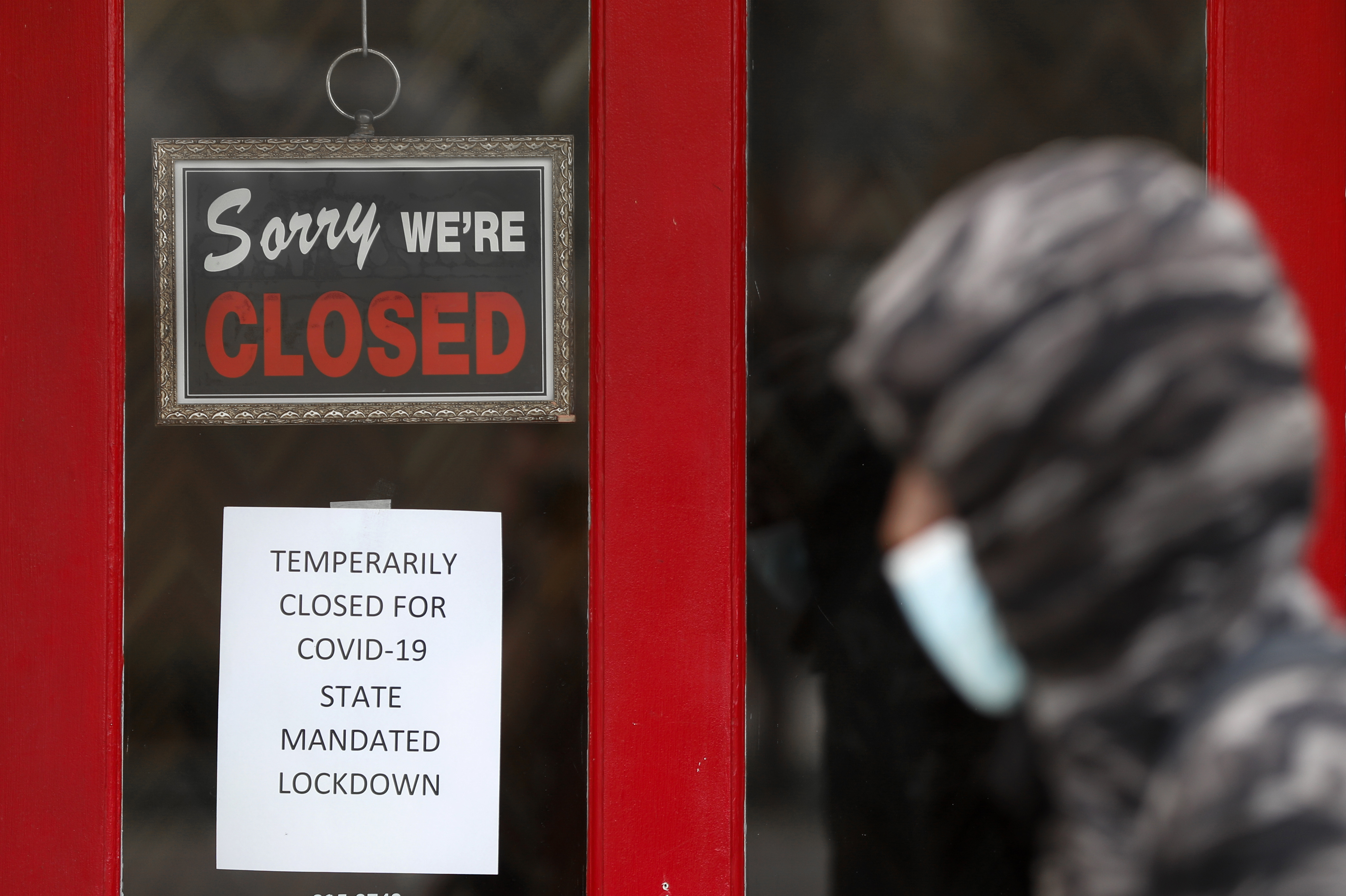 A pedestrian walks by The Framing Gallery, closed due to the Covid-19 pandemic, in Grosse Pointe, Michigan, on May 7.