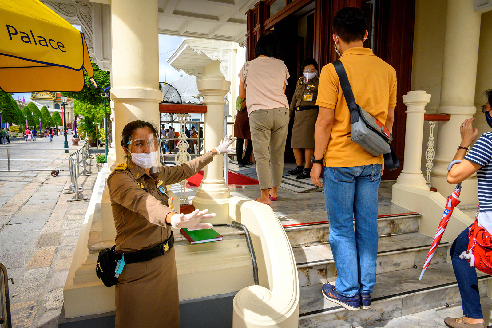 An officer enforces social distancing at the entrance of the Grand Palace in Bangkok on June 7, as it reopened for visitors following restrictions to halt the spread of Covid-19.