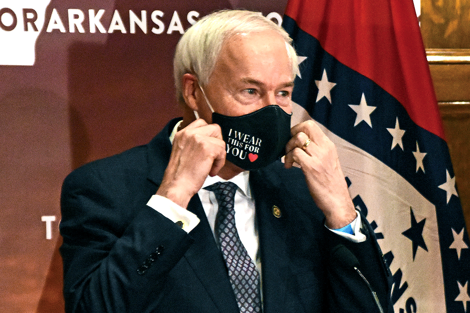 Gov. Asa Hutchinson removes his mask before a briefing at the state capitol Monday' July 20, 2020 in Little Rock.