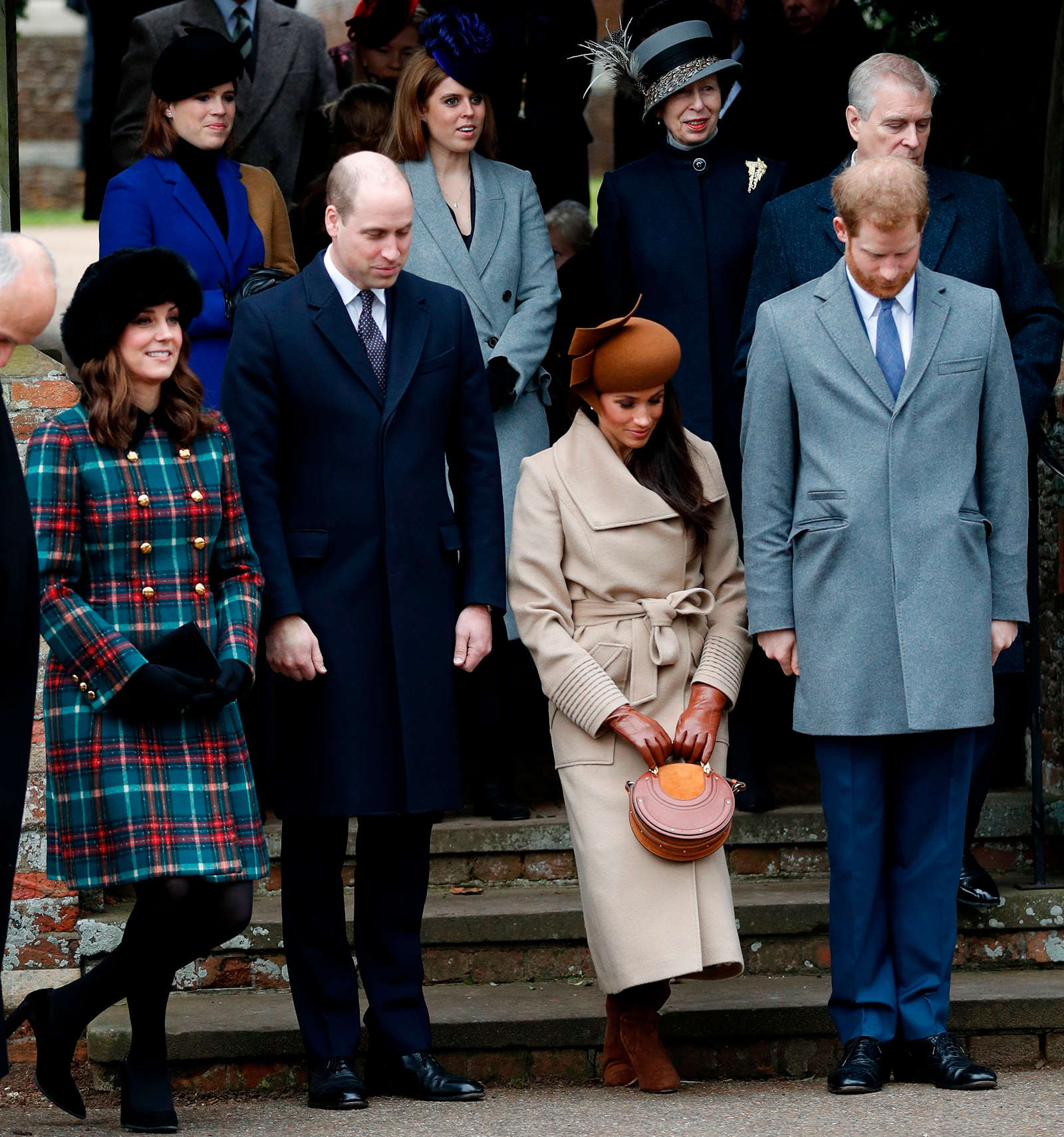 Meghan Markle curtsies as she sees off Britain's Queen Elizabeth II leaving after the Royal Family's traditional Christmas Day church service at St Mary Magdalene Church in Sandringham, Norfolk, eastern England, on December 25, 2017.