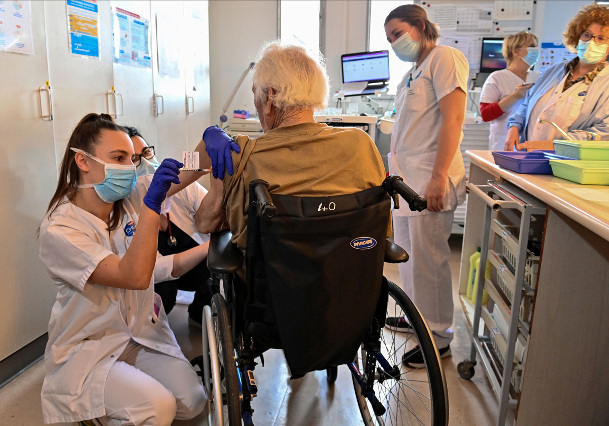 A nurse administers a dose of the Pfizer-BioNtech Covid-19 vaccine to an elderly person in the Bellevue gerontology center in Montpellier, France on January 4