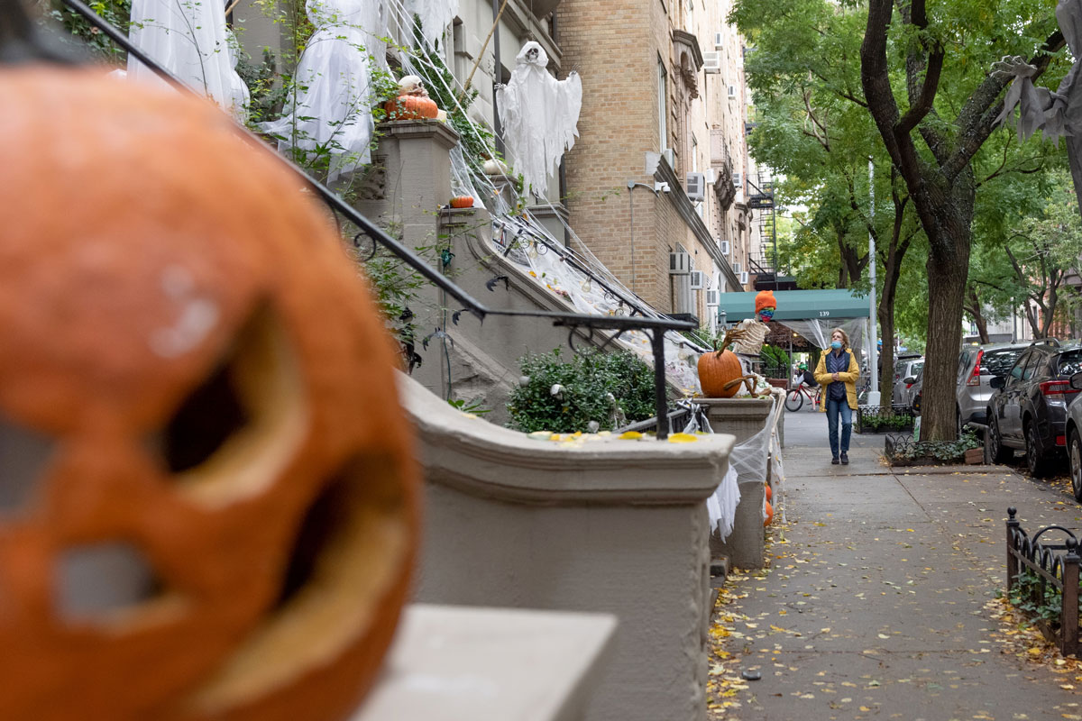 A woman wearing a mask looks up at an Upper West Side home decorated for Halloween on October 28 in New York City.