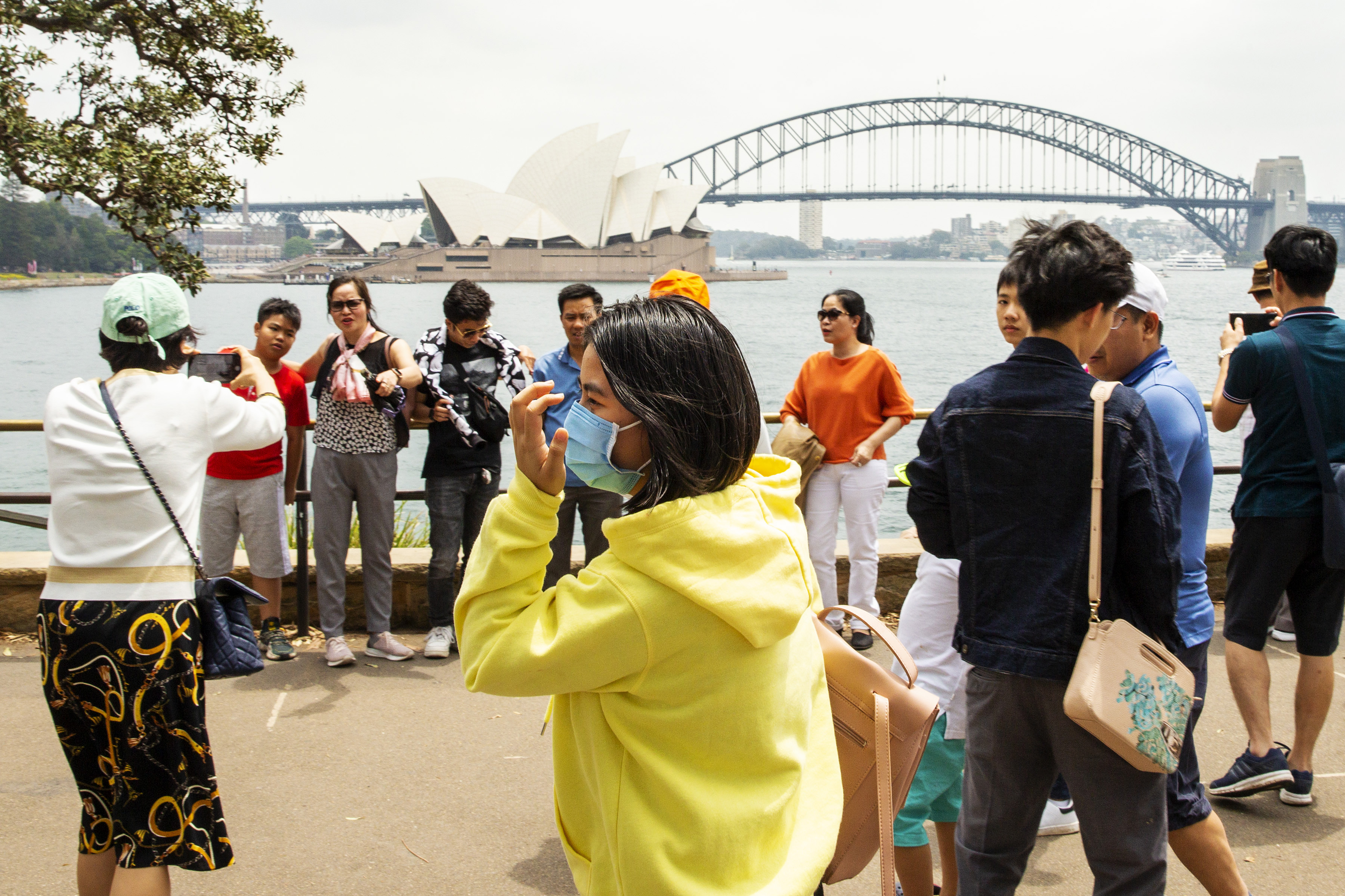 Tourists wear protective masks in Sydney.