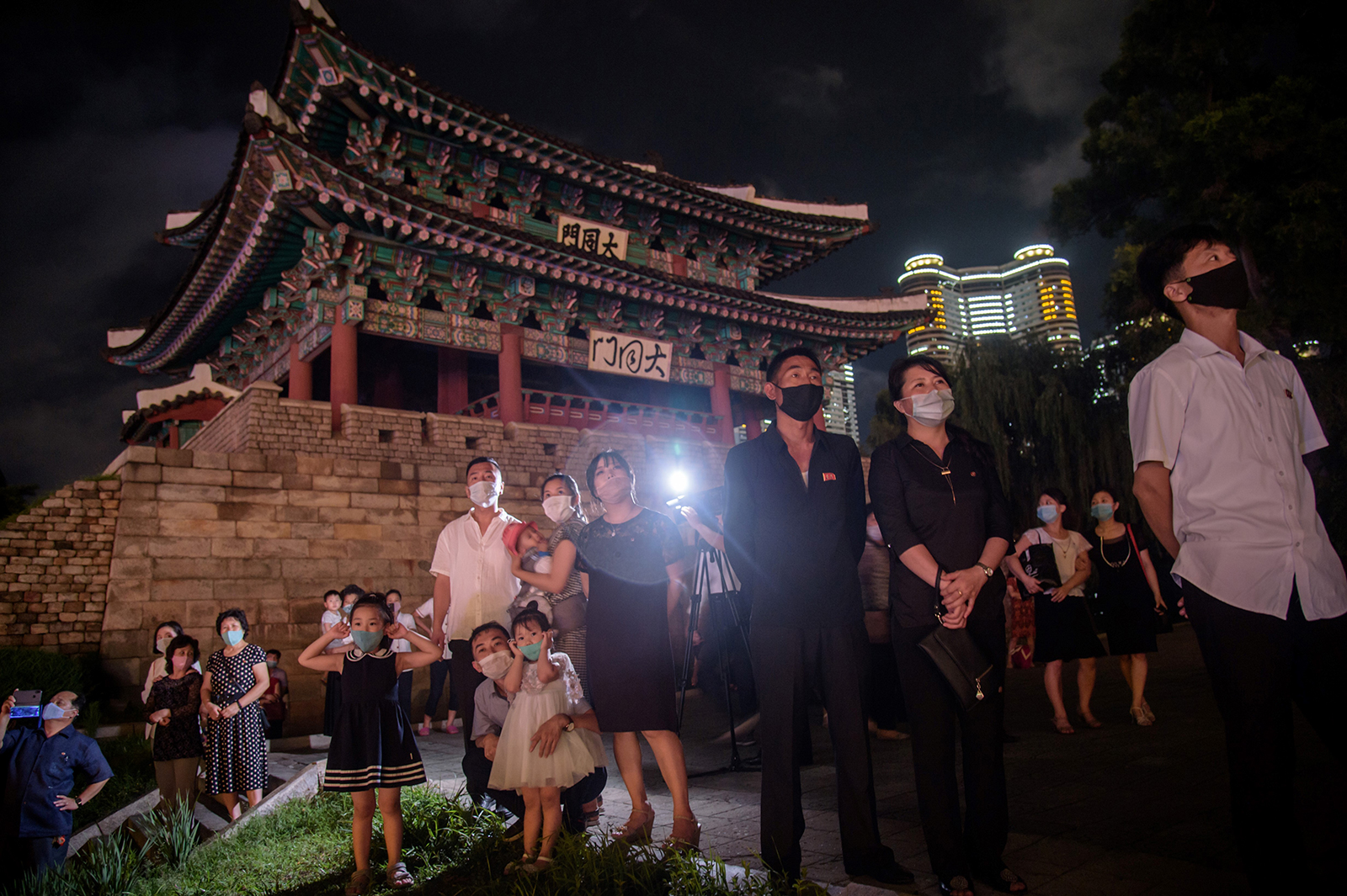 People stand at Taedongmun gate in Pyongyang to watch a firework display on July 27 to mark the 67th anniversary of the signing of the Korean War armistice agreement.