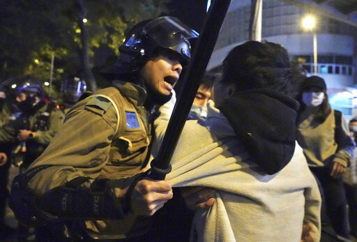 A local resident struggles with riot police in Hong Kong on Sunday.