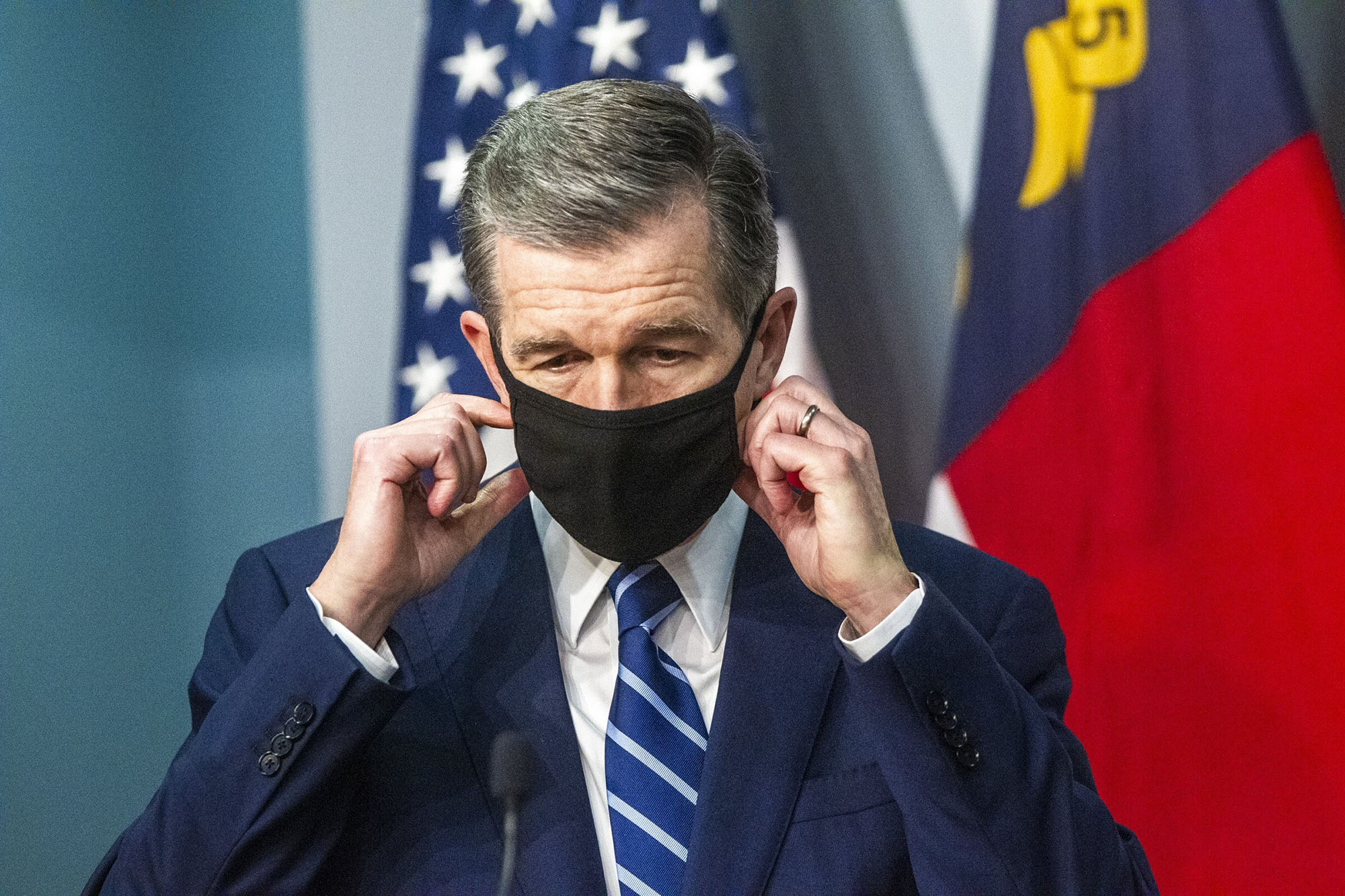 Gov. Roy Cooper removes his mask before speaking at a briefing on the state's coronavirus pandemic response at the N.C. Emergency Operations Center in Raleigh, North Carolian, on December 8.