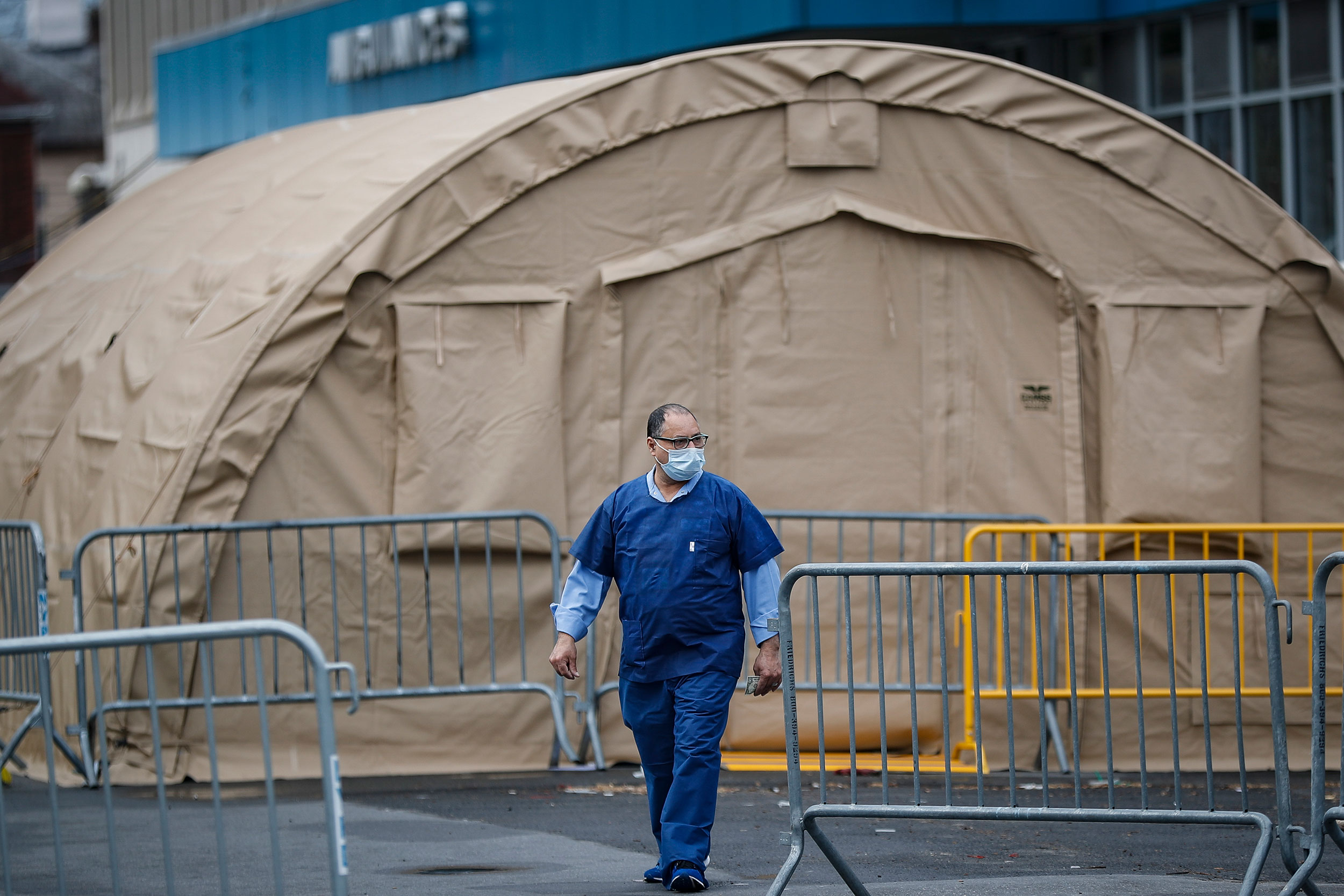 A medical worker walks past a testing tent outside SUNY Downstate Medical Center on March 27.