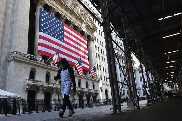 A person walks past the New York Stock Exchange at Wall Street on November 16, 2020.