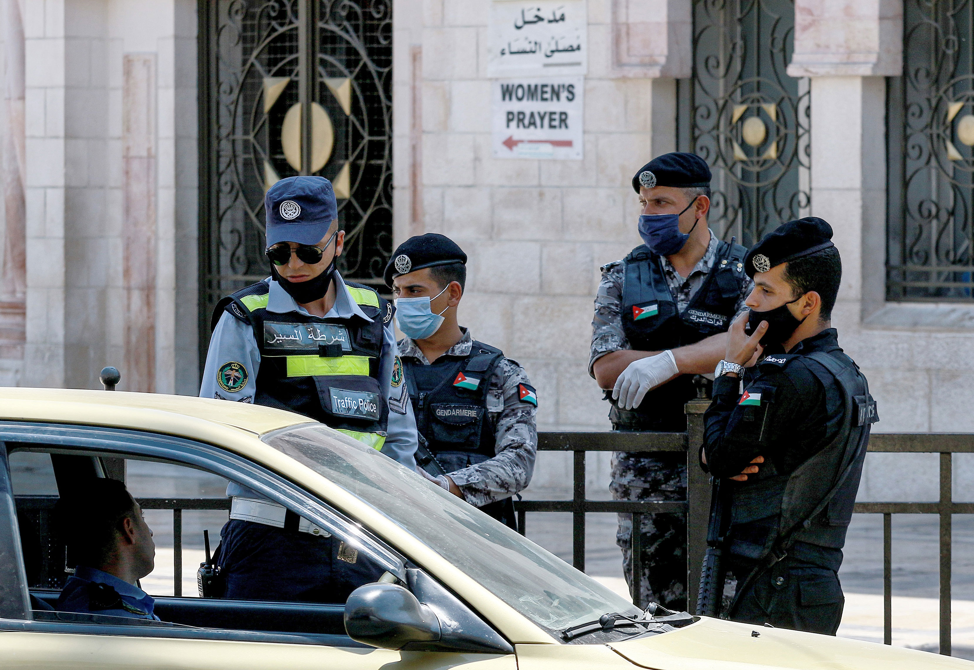 Police officers stop a vehicle outside the Grand Husseini Mosque in Amman, Jordan, while enforcing a curfew on August 28.