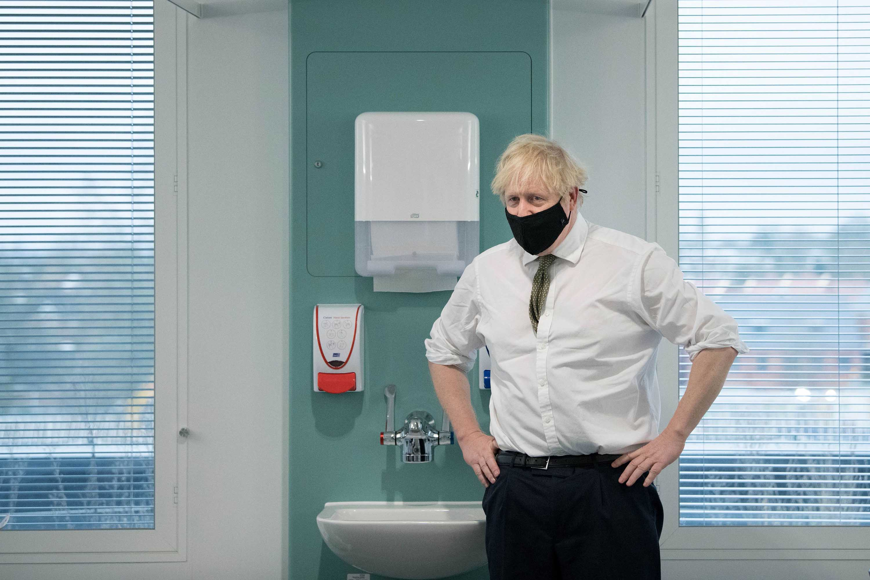 British Prime Minister Boris Johnson speaks to staff during a visit to London's Chase Farm Hospital on January 4, during the rollout of the newly approved AstraZeneca/Oxford Covid-19 vaccine.