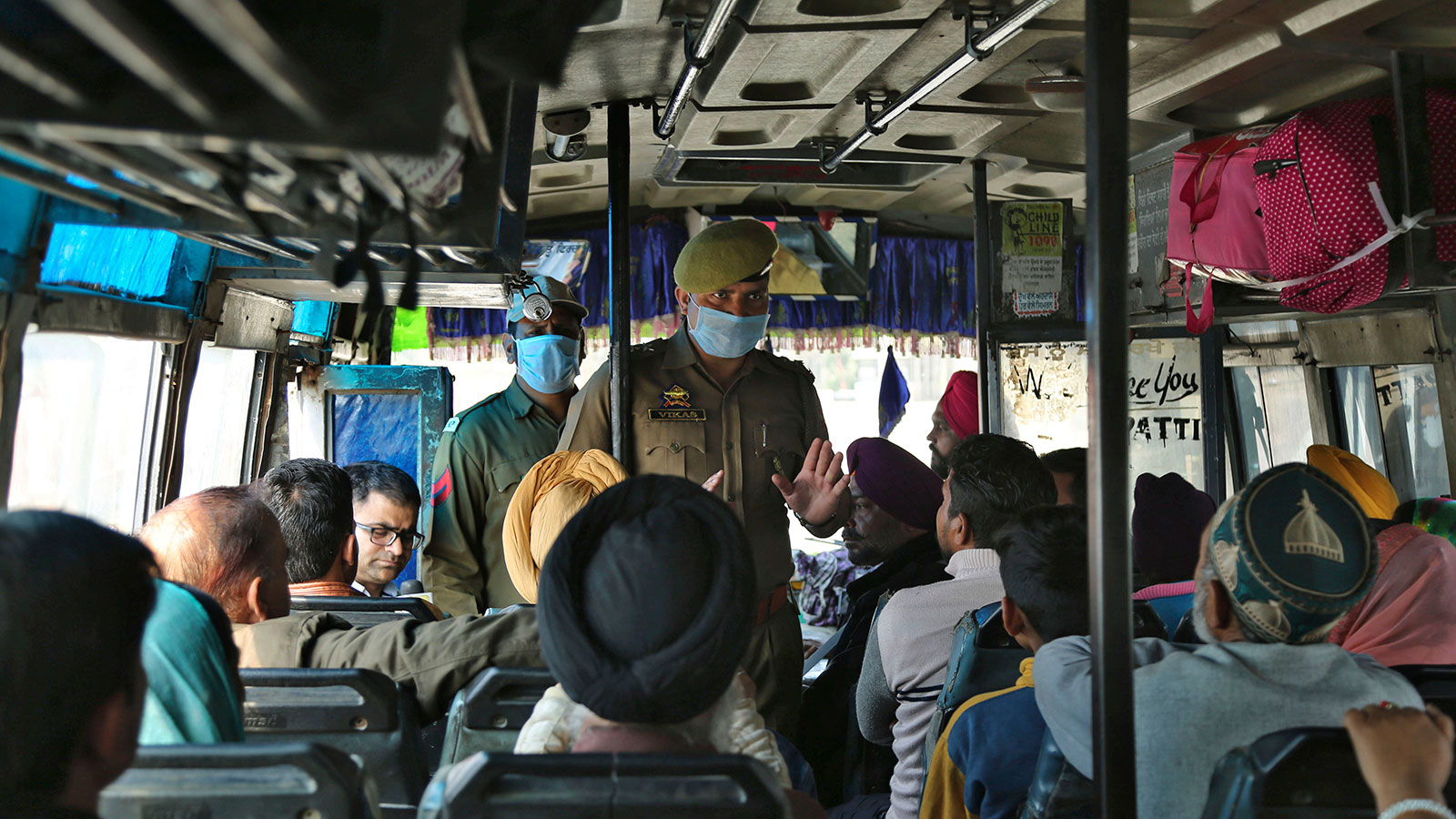 A Jammu and Kashmir police officer briefs bus passengers about the coronavirus in Lakhanpur, India on March 4.