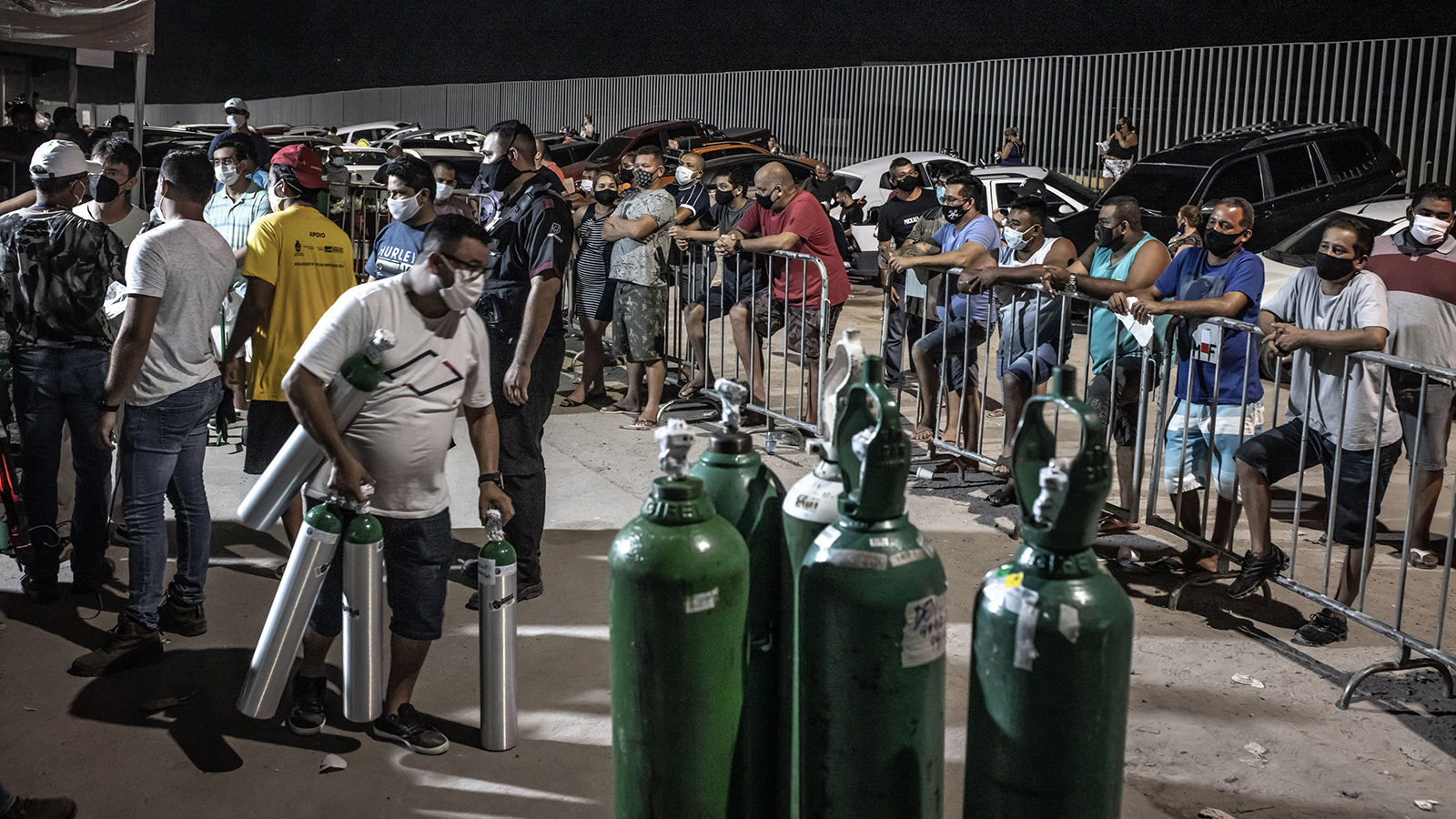 People wearing protective masks wait in line to refill oxygen tanks in Manaus, Brazil, on Sunday, January 17.