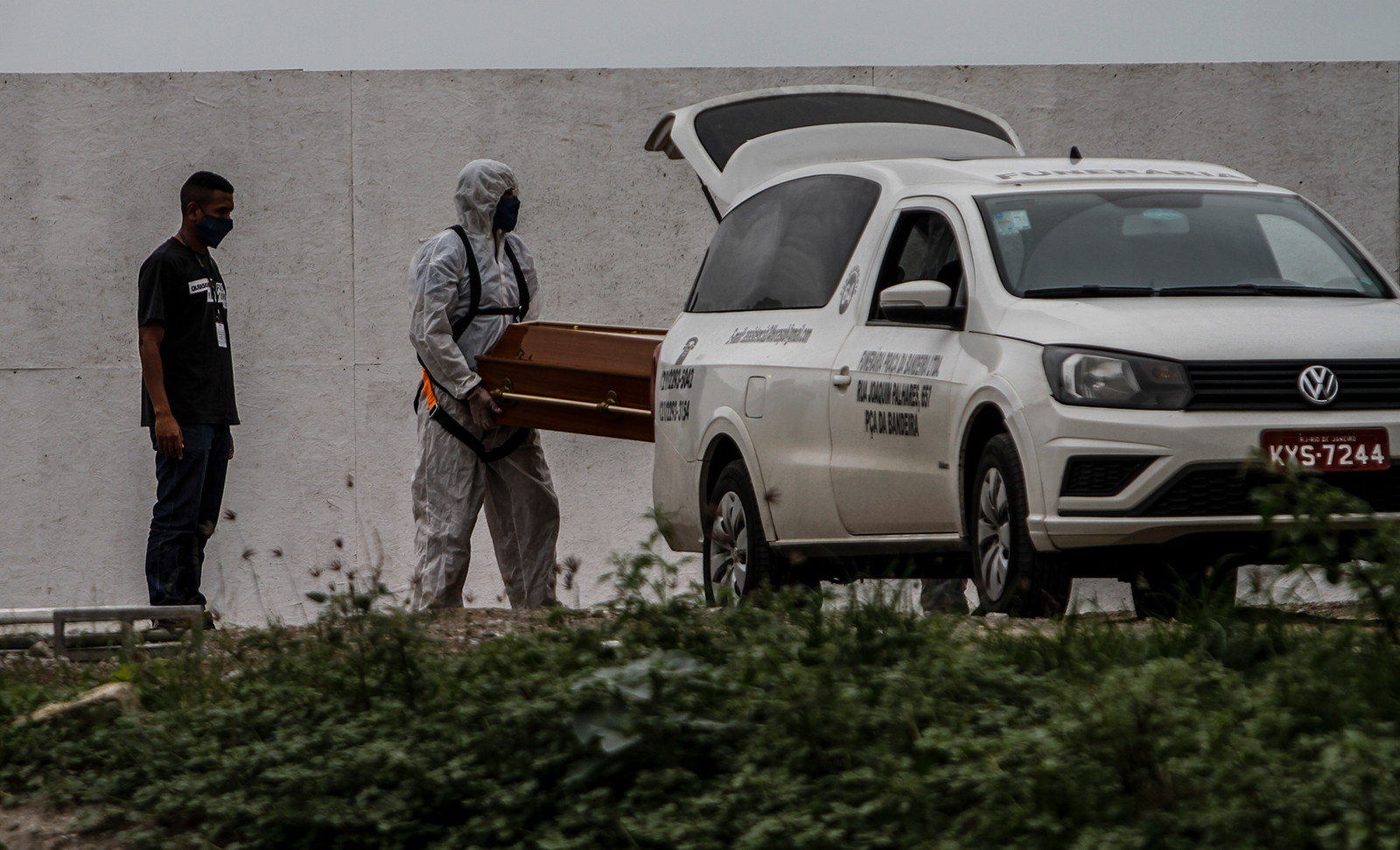 Cemetery workers in protective suits carry a coffin at the Caju cemetery amidst the coronavirus pandemic on July 16, in Rio de Janeiro.