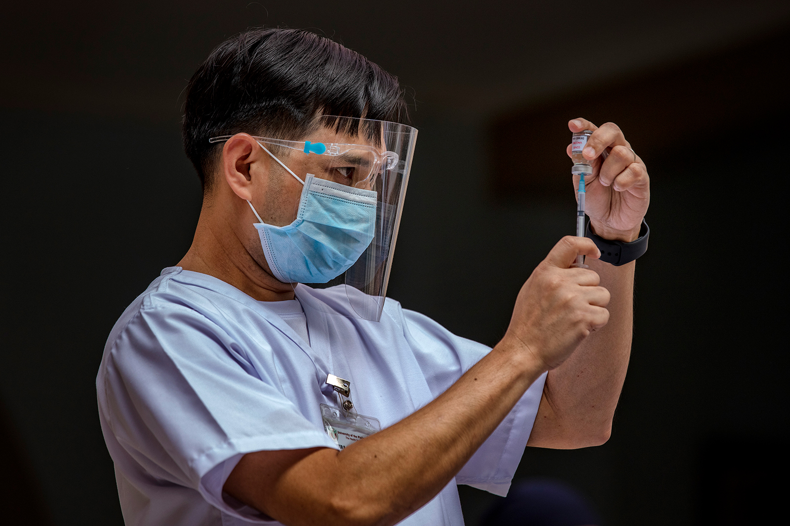 A health worker takes a mock Covid-19 vaccine from a box during a mock vaccination drill at the Philippine General Hospital in Manila, Philippines, on February 15.