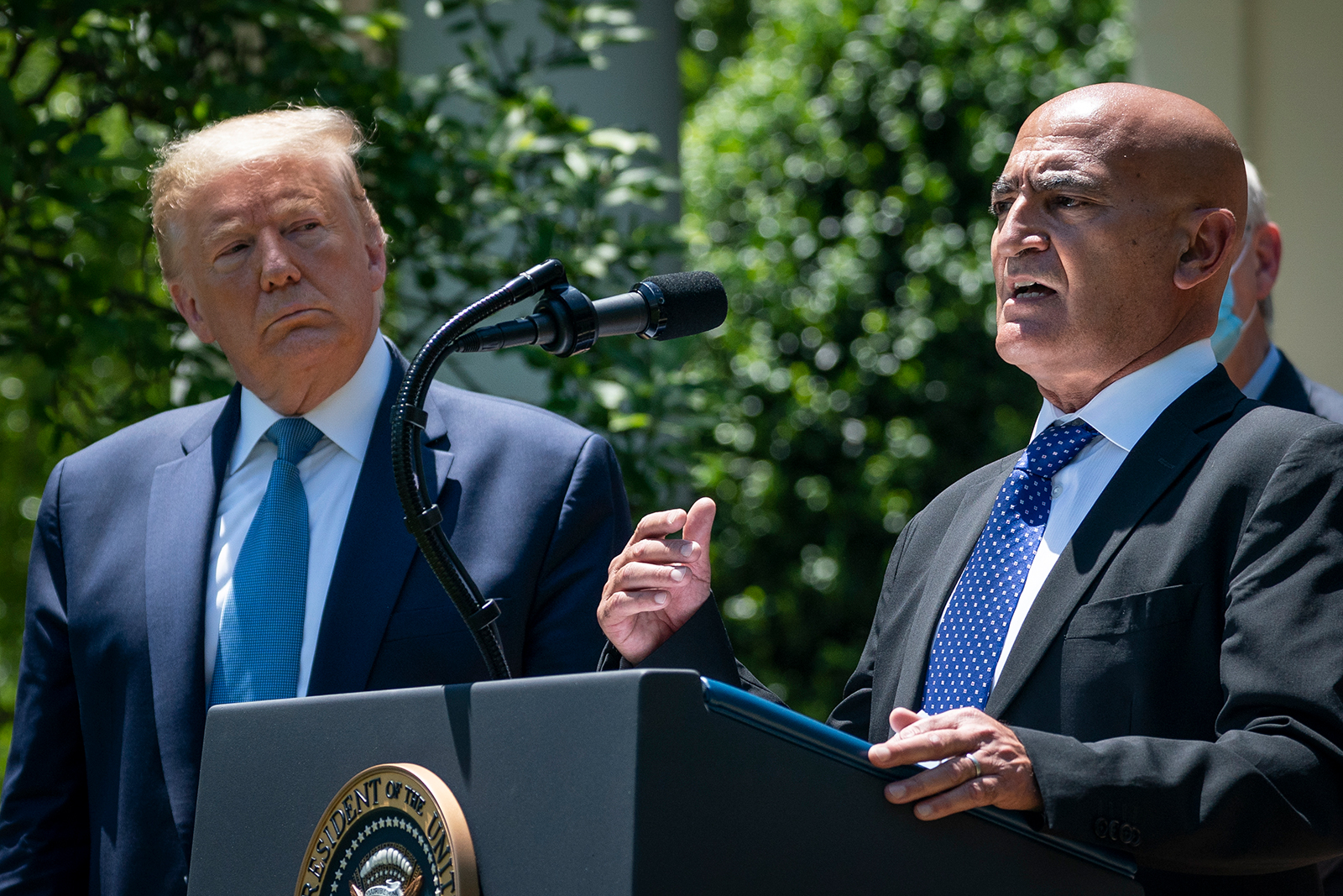 President Donald Trump listens as Moncef Slaoui, the head of the US government's effort to develop avaccine against Covid-19, speaks about coronavirus vaccine development in the Rose Garden of the White House, in Washington, DC on May 15.