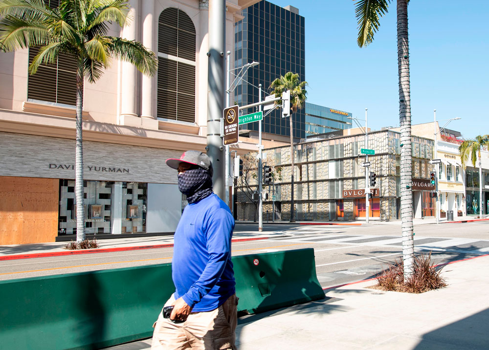 A person wearing a mask walks on Rodeo Drive in Beverly Hills, California on April 1.