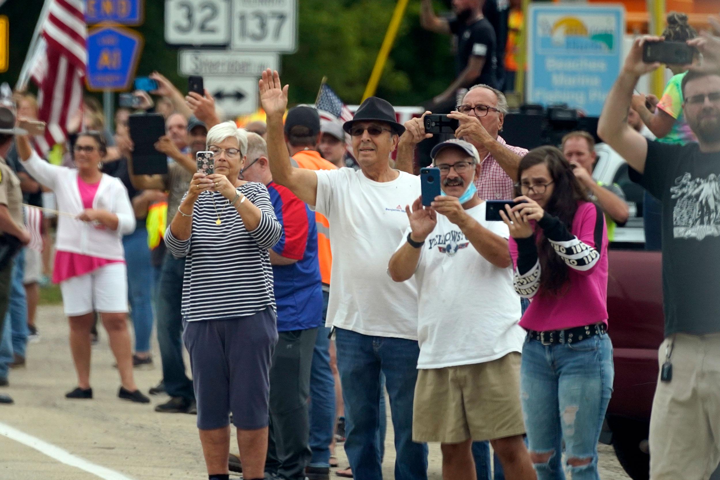 People wave at President Trump's motorcade in Kenosha on September 1.