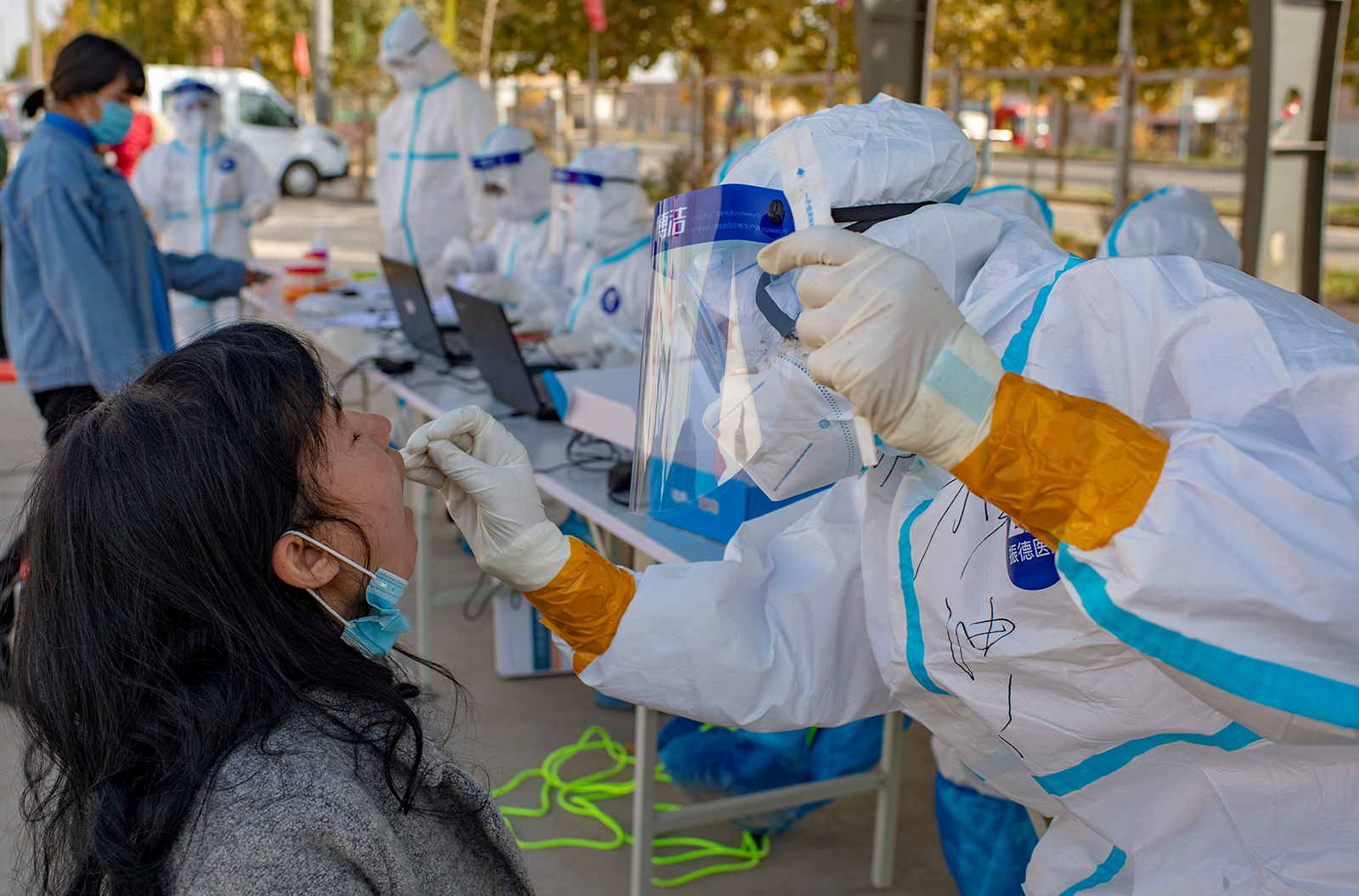 A medical worker collects a sample from a person for nucleic acid testing in Shufu County of Kashgar Prefecture, northwest China's Xinjiang Uygur Autonomous Region, on October 26.