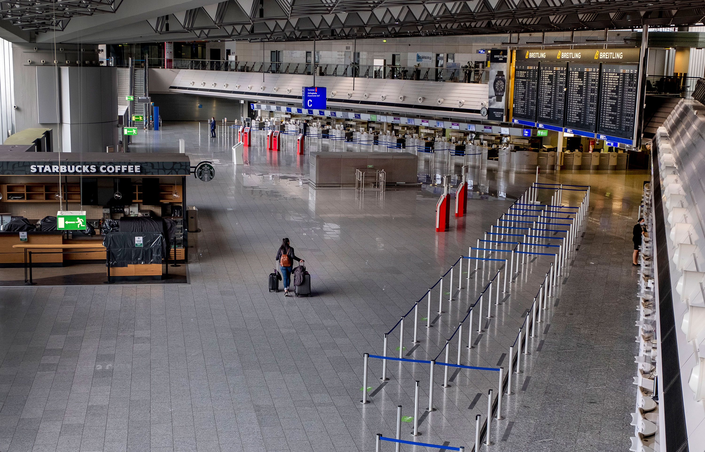 A passenger walks through a nearly empty airport in Frankfurt, Germany, on April 9.