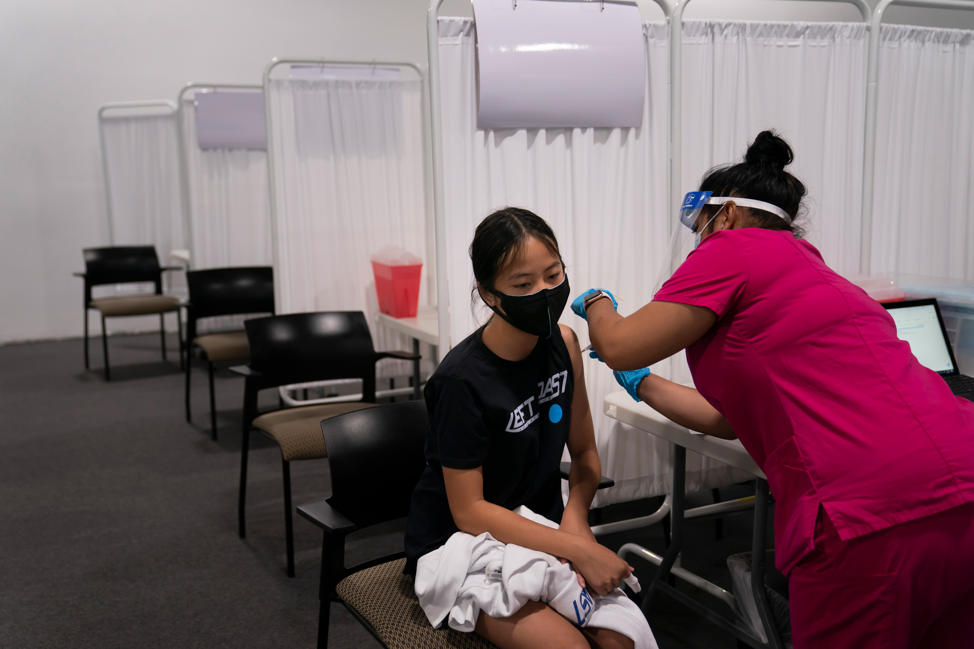 Payton Nguyen, 12, receives her first dose of the Pfizer COVID-19 vaccine from medical assistant Gloria Urgell at Providence Edwards Lifesciences vaccination site in Santa Ana, California, on May 13.