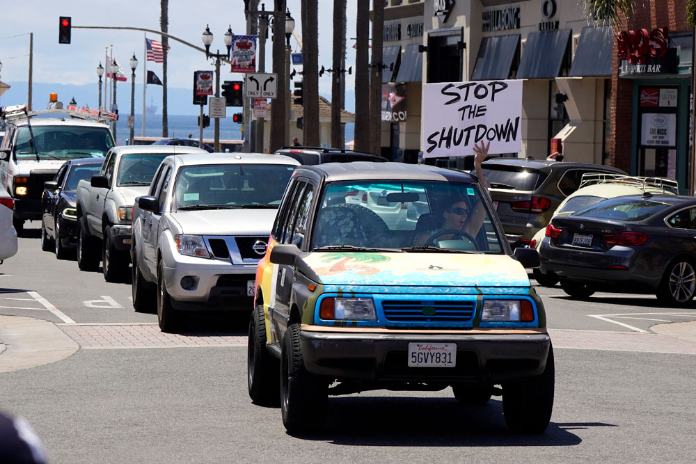 A driver waves a sign at other protesters who were demonstrating against stay-at-home orders that were put in place due to the coronavirus outbreak on Friday, April 17, in Huntington Beach, Calif.