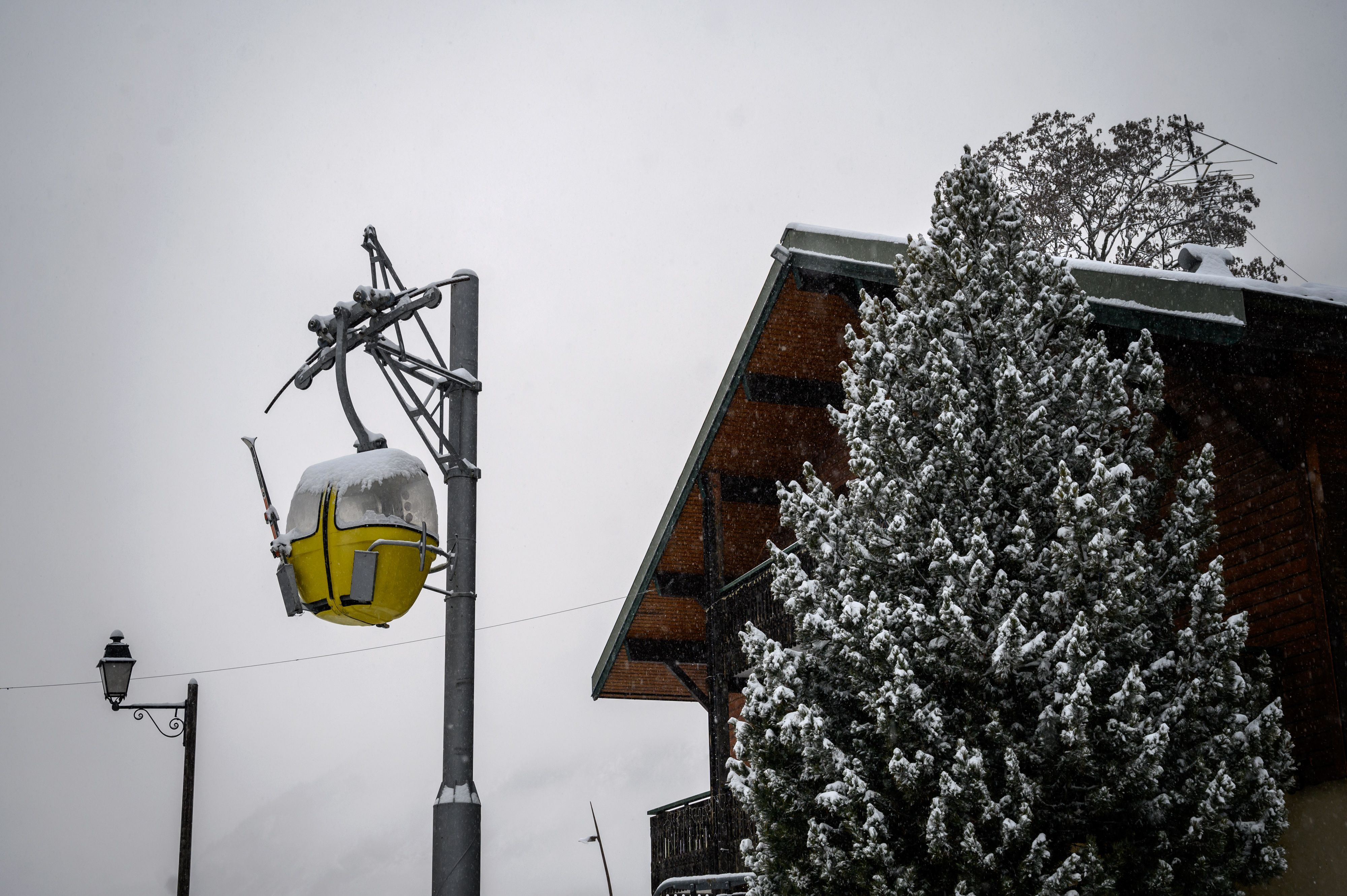 A snow covered gondola is seen hanging from a pole on December 1, in La Chapelle-d'Abondance, eastern France, a few kilometers from neighbouring Switzerland and its ski resorts.