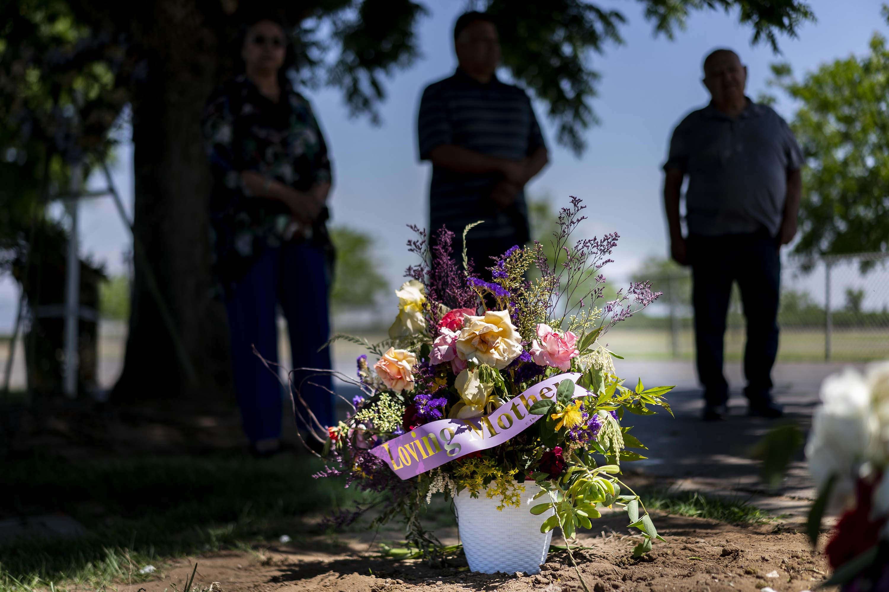 Family members of Hortensia Sosa, who died from COVID-19 at a nursing home in Visalia, California, mourn over her grave in Dinuba, California, on May 3.