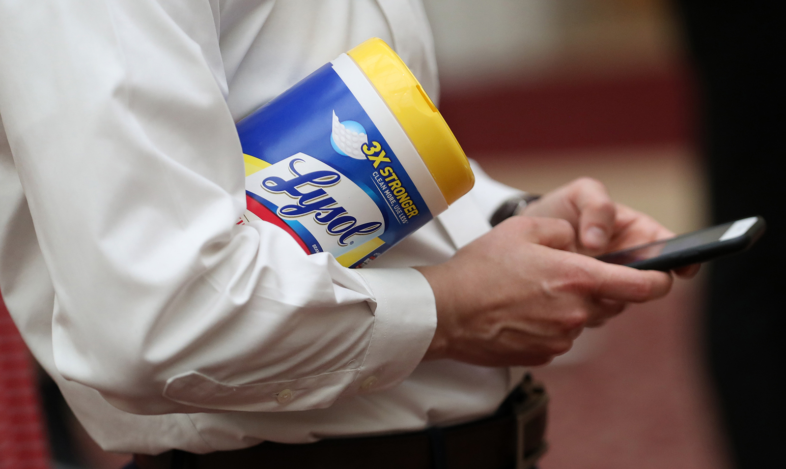 An attendee holds a container of Lysol disinfecting wipes as San Francisco Mayor London Breed speaks during a press conference on March 16 in San Francisco, California.